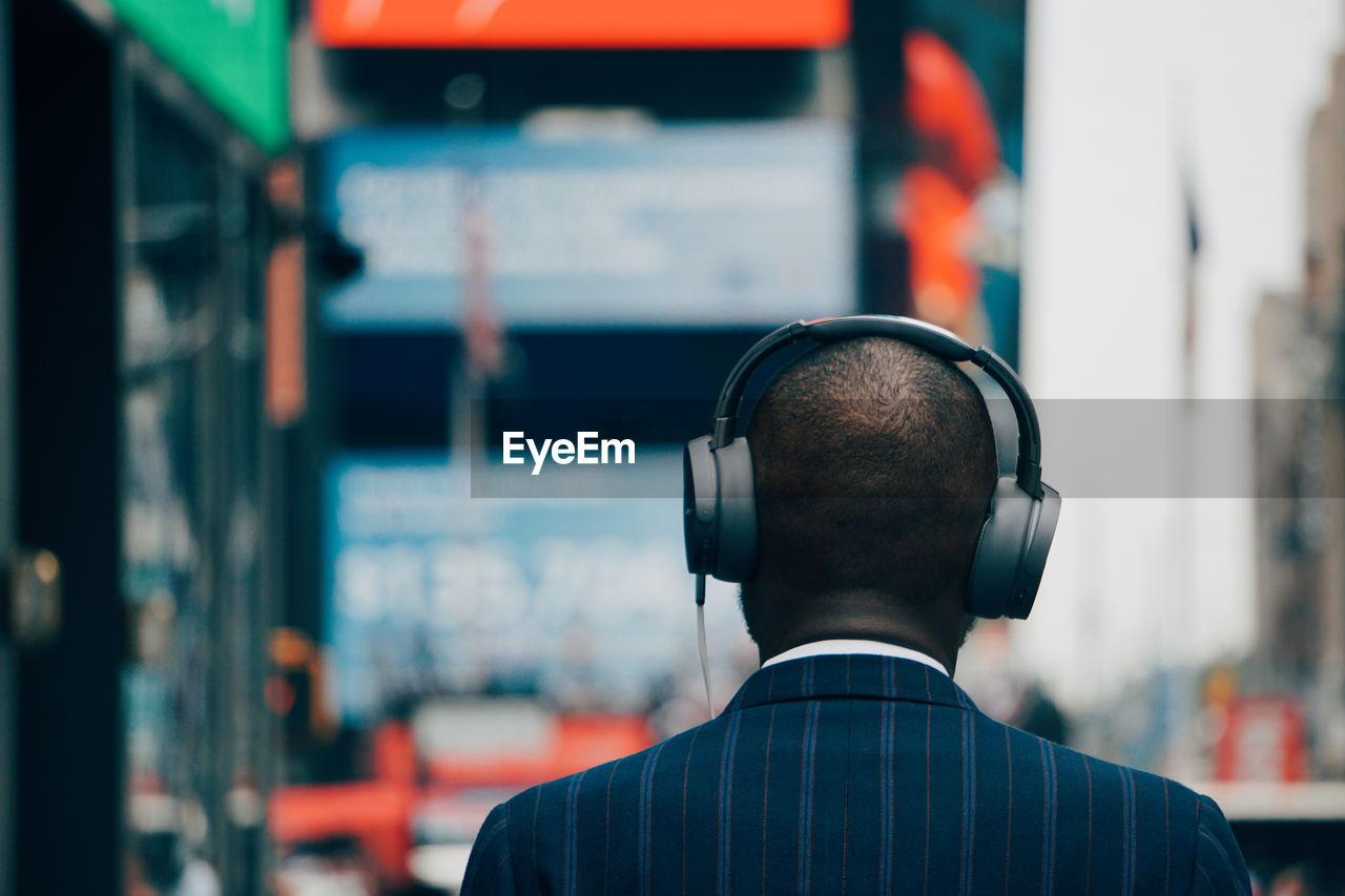 Rear View Of Businessman Wearing Headphones