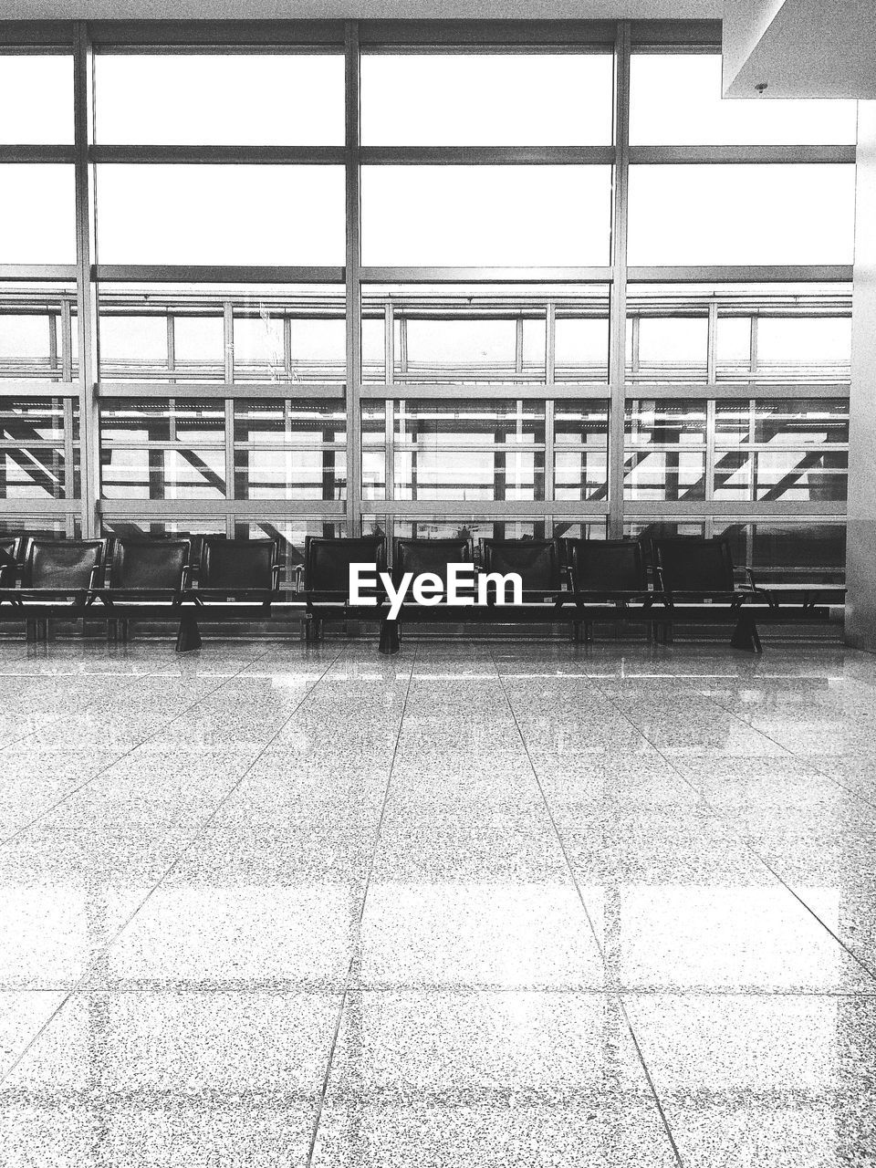 Empty chairs against glass windows at airport