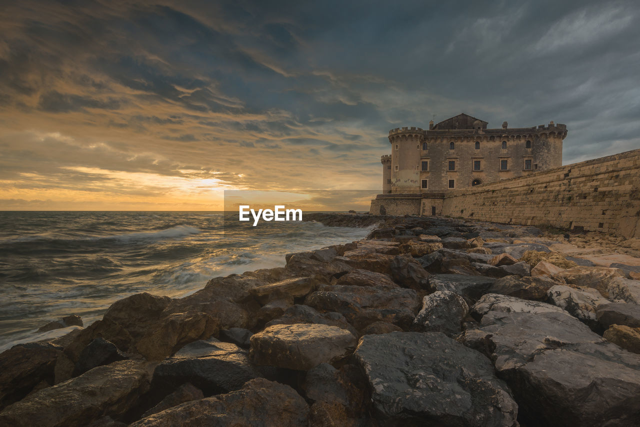 sky, sea, water, rock, cloud - sky, rock - object, architecture, solid, sunset, built structure, horizon over water, beach, history, the past, land, horizon, nature, building exterior, scenics - nature, no people, outdoors, ancient civilization, ruined