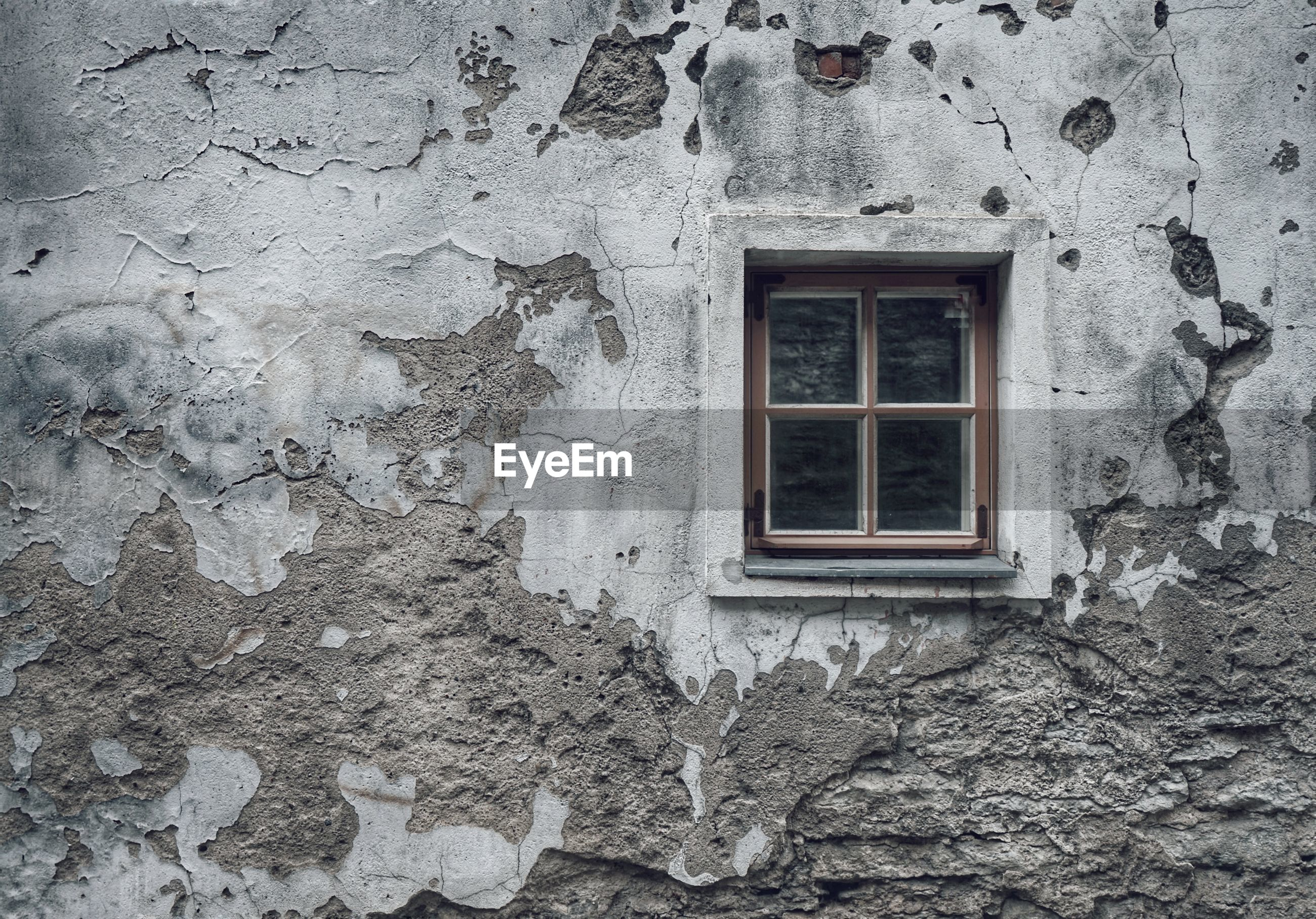 Low angle view of window on wall of old building