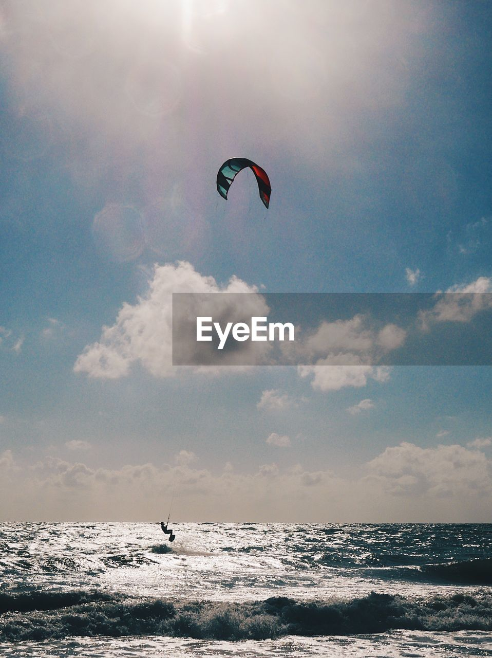Person kiteboarding over sea against sky