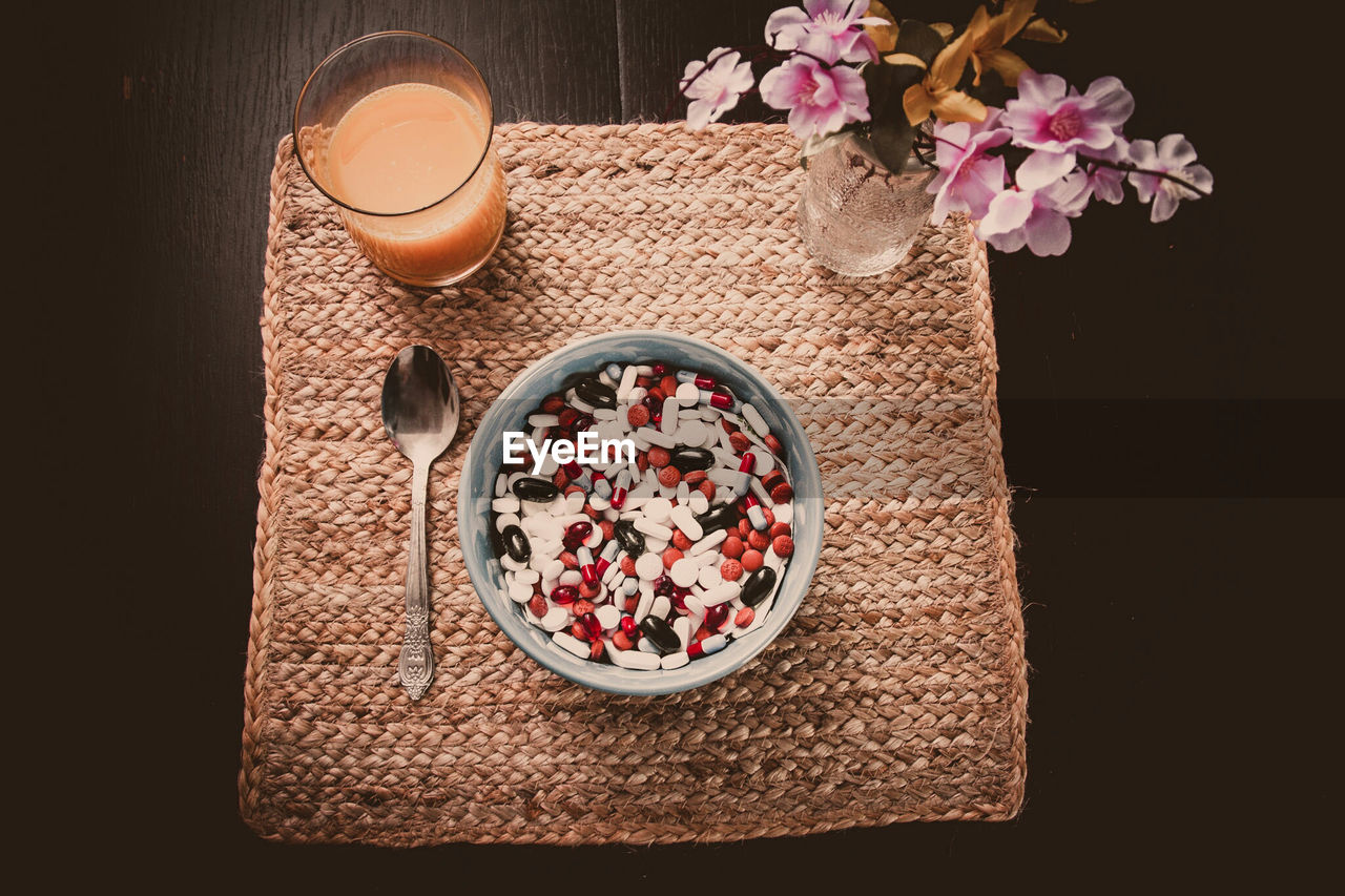 High angle view of bowl full of pills with glass of juice