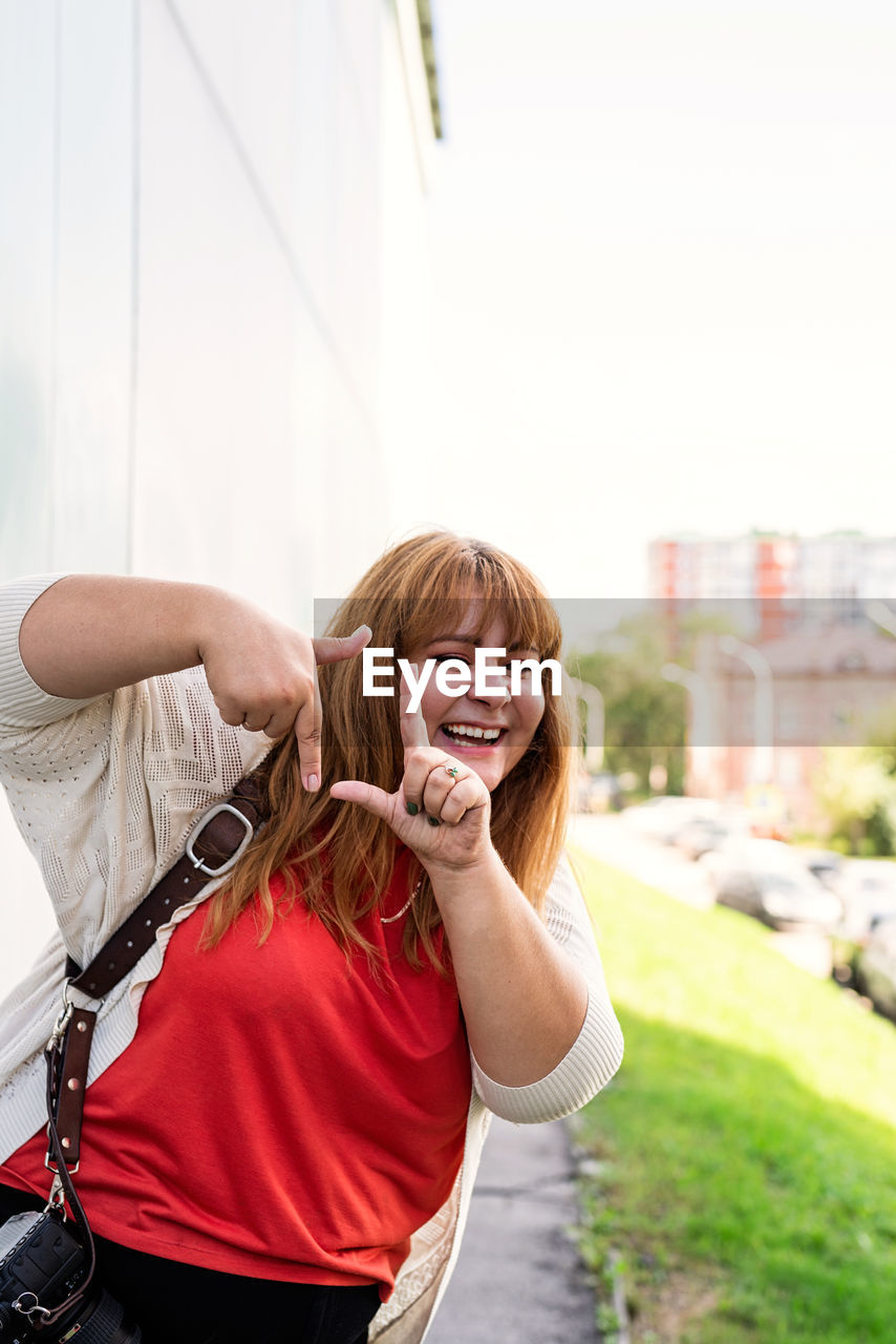 Body positive. young woman taking picture with imaginary camera