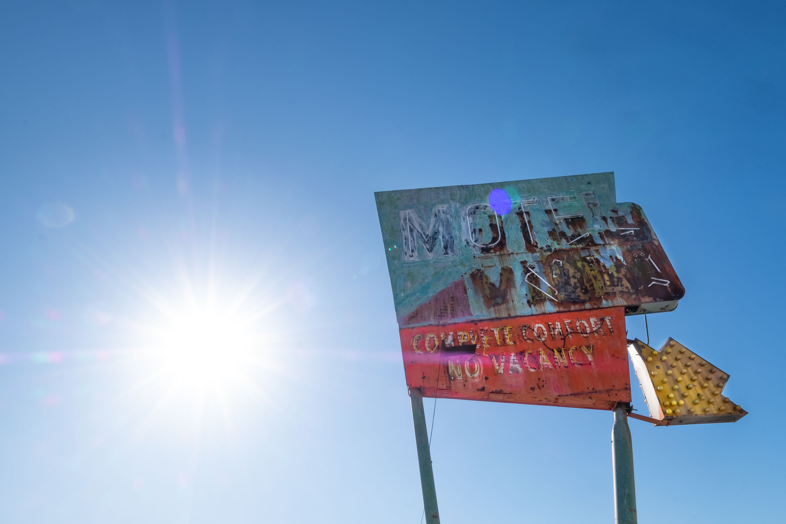 LOW ANGLE VIEW OF INFORMATION SIGN AGAINST BRIGHT SUN