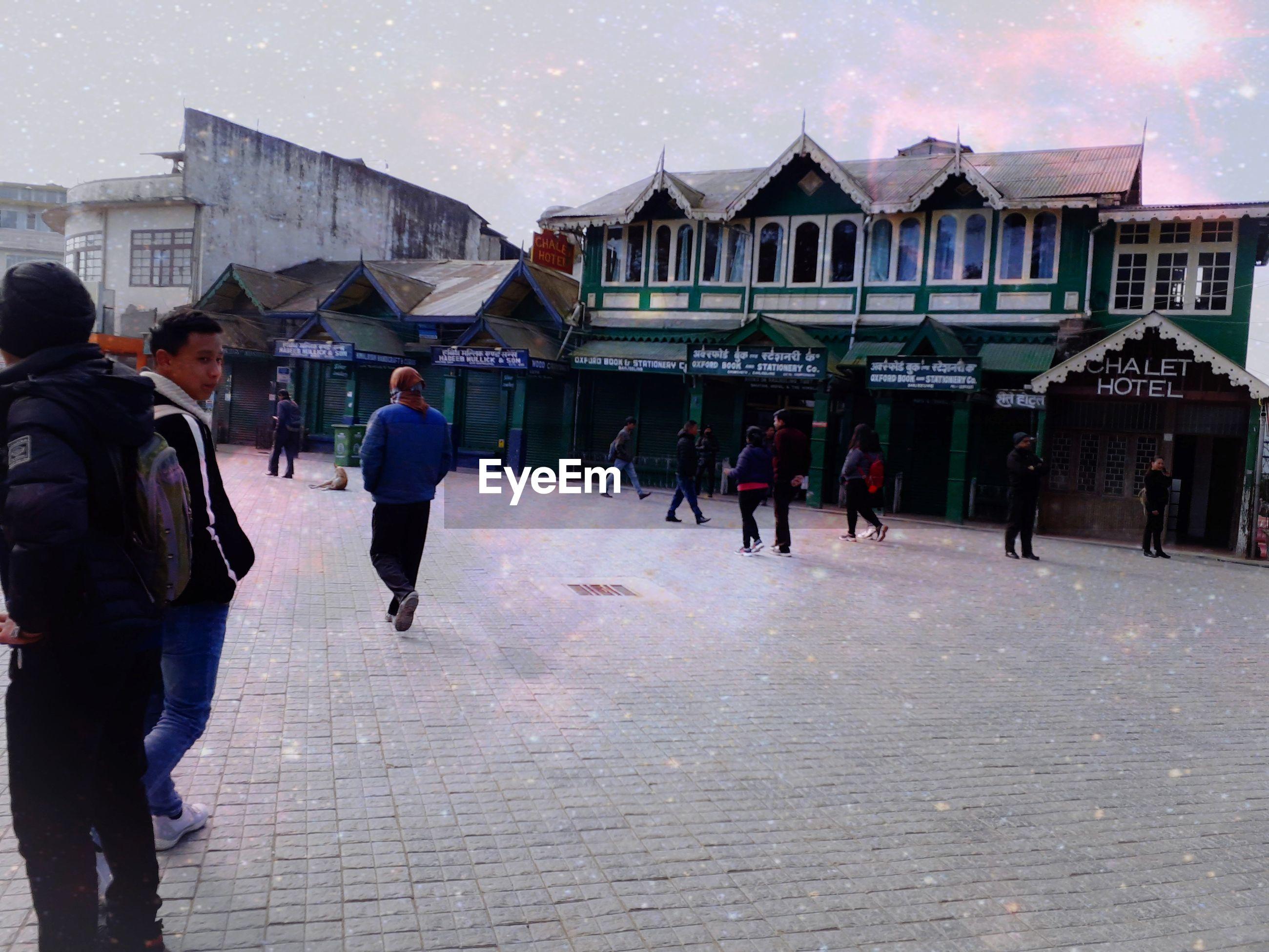 PEOPLE WALKING ON STREET AGAINST BUILDINGS