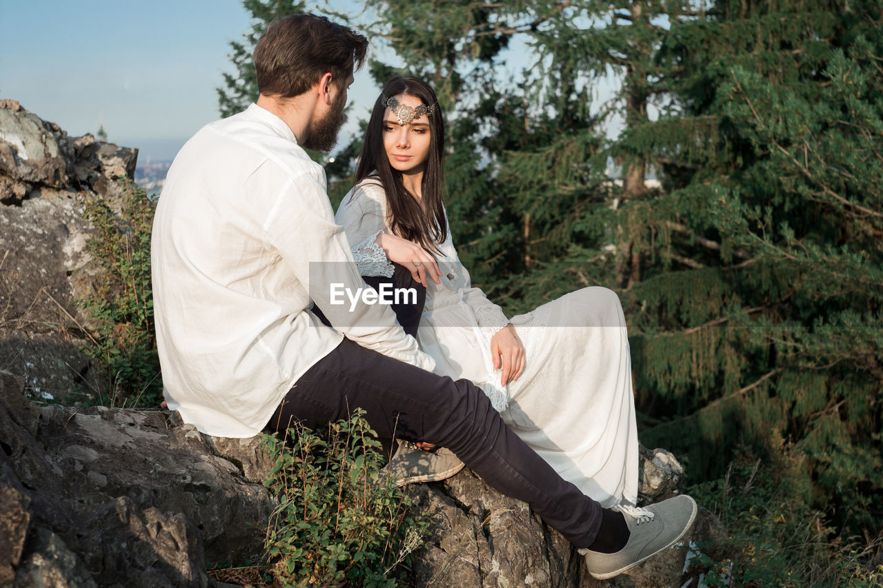 Romantic couple sitting on mountain against sky