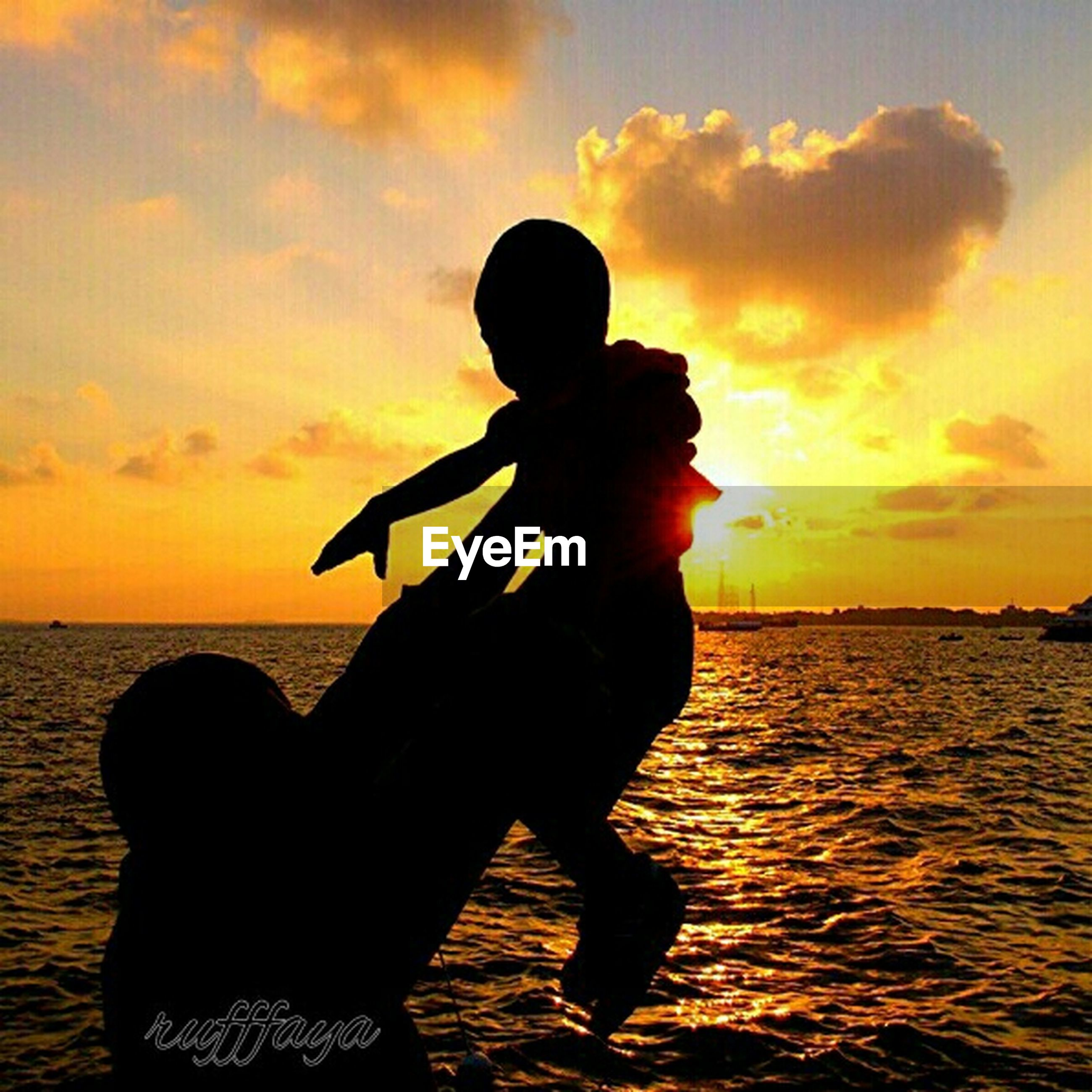 sunset, sea, sky, lifestyles, water, leisure activity, silhouette, horizon over water, orange color, beach, childhood, cloud - sky, standing, three quarter length, beauty in nature, sun, holding, shore