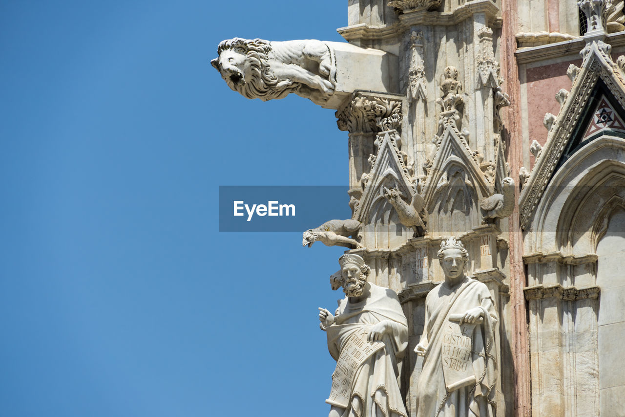sculpture, statue, representation, art and craft, human representation, architecture, built structure, low angle view, sky, the past, creativity, history, craft, day, clear sky, building exterior, no people, male likeness, belief, religion, gargoyle, ornate, architectural column, ancient civilization