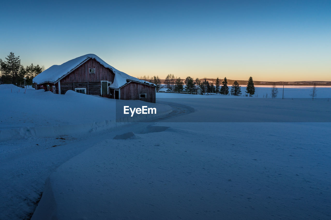 Houses on snow covered landscape against clear sky
