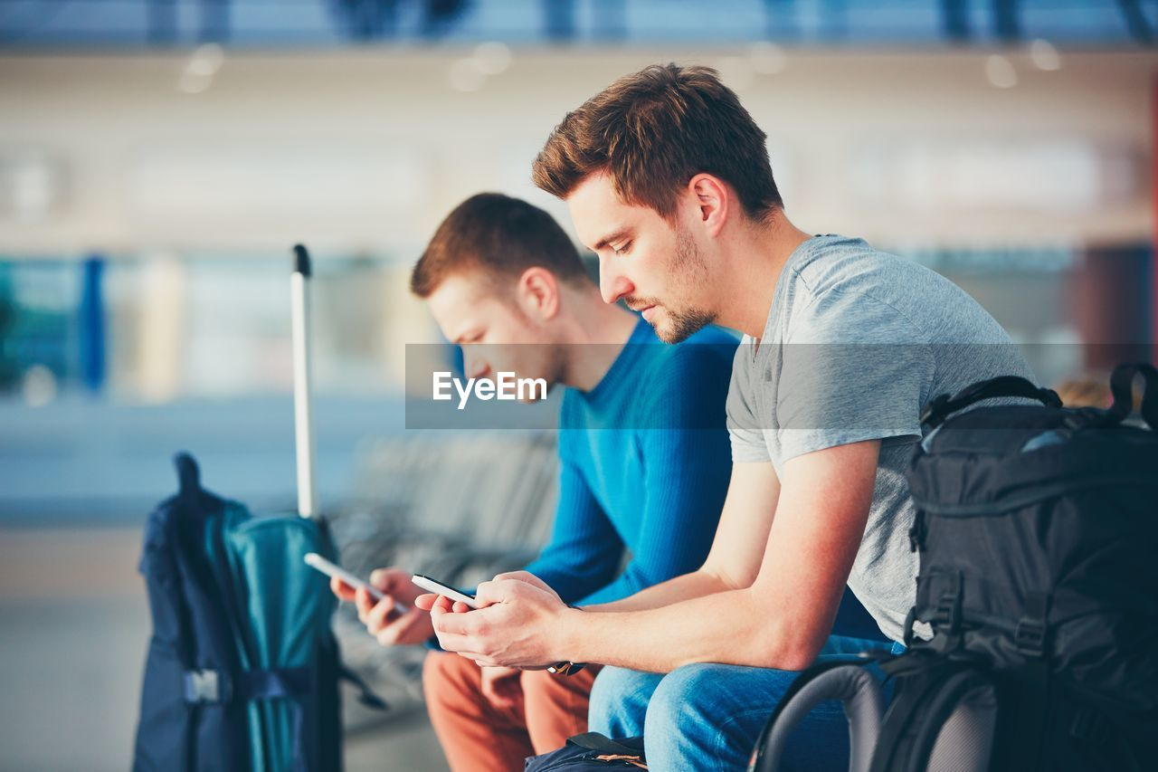 Friends Using Phones While Waiting At Airport Departure Area
