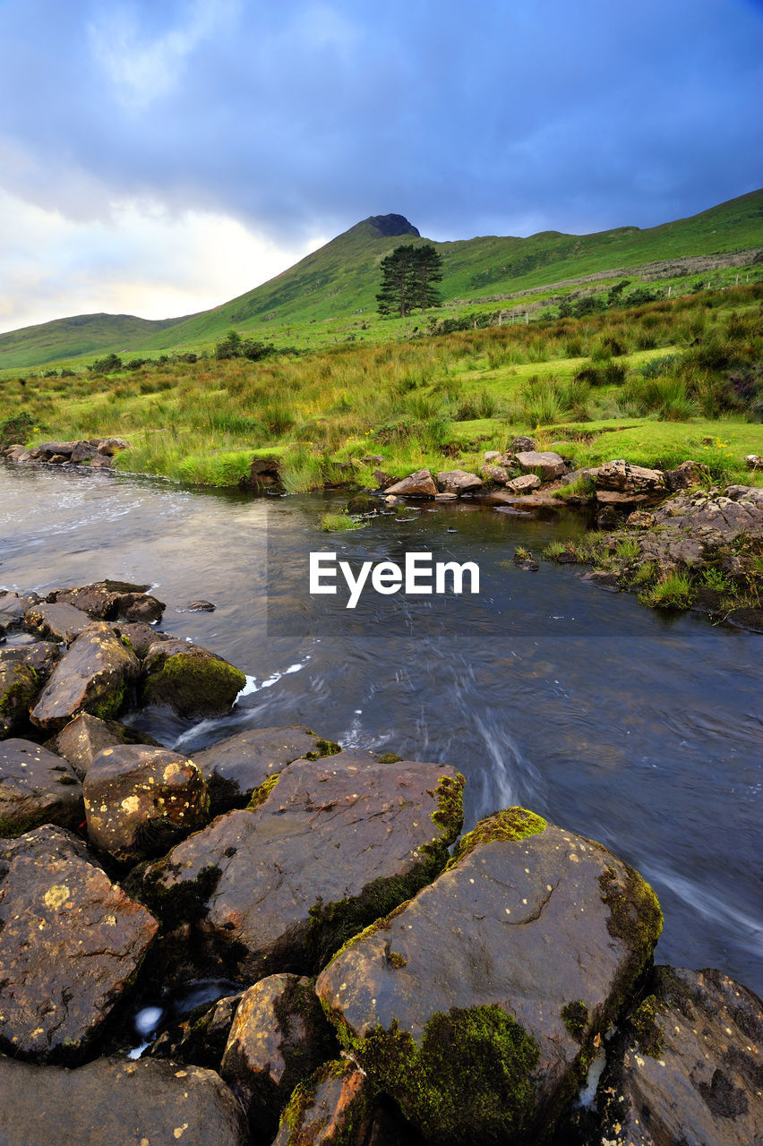 water, scenics - nature, rock, tranquil scene, tranquility, sky, cloud - sky, no people, beauty in nature, solid, nature, day, rock - object, environment, non-urban scene, mountain, green color, plant, land, outdoors, flowing water