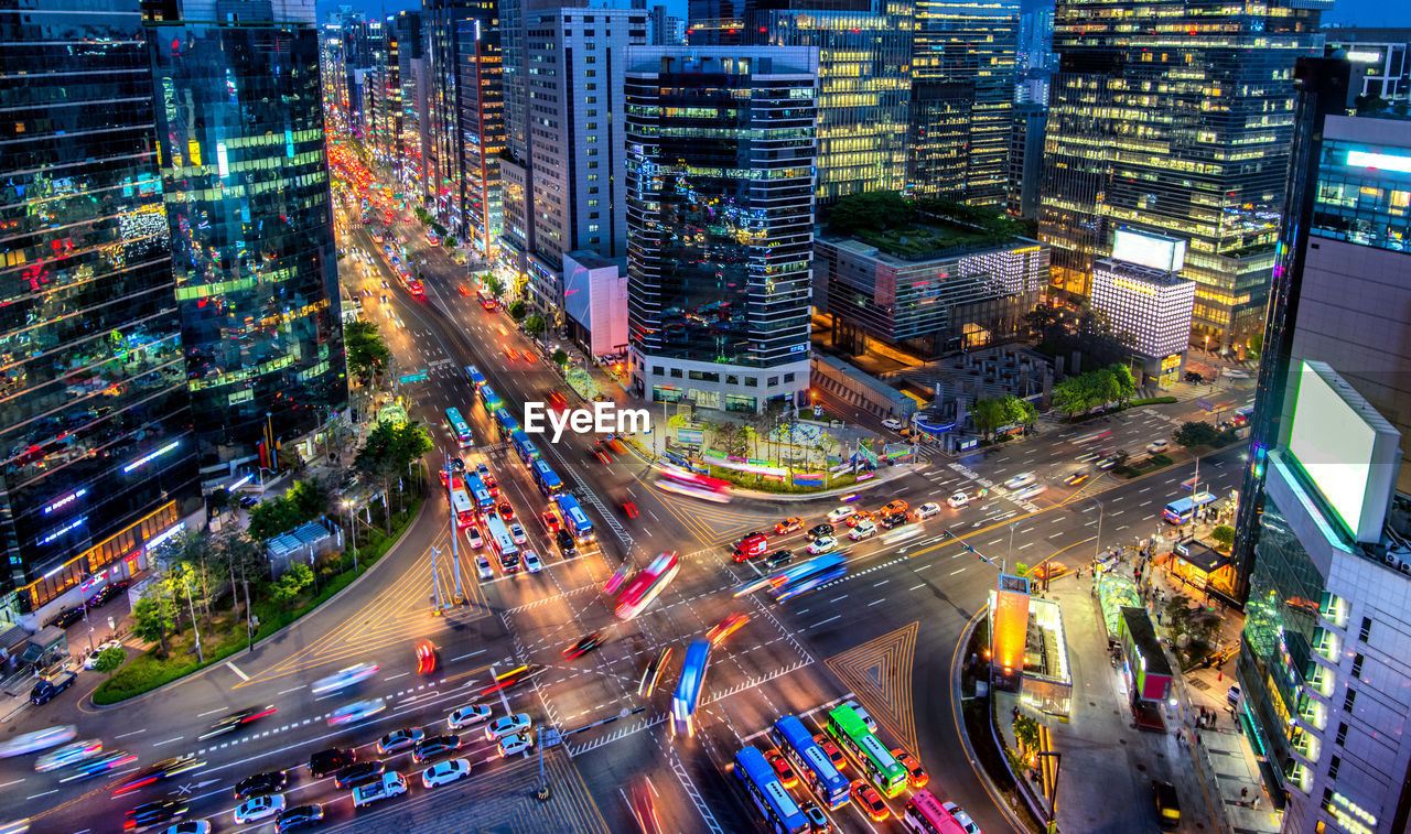 High angle view of vehicles on road in illuminated city at night