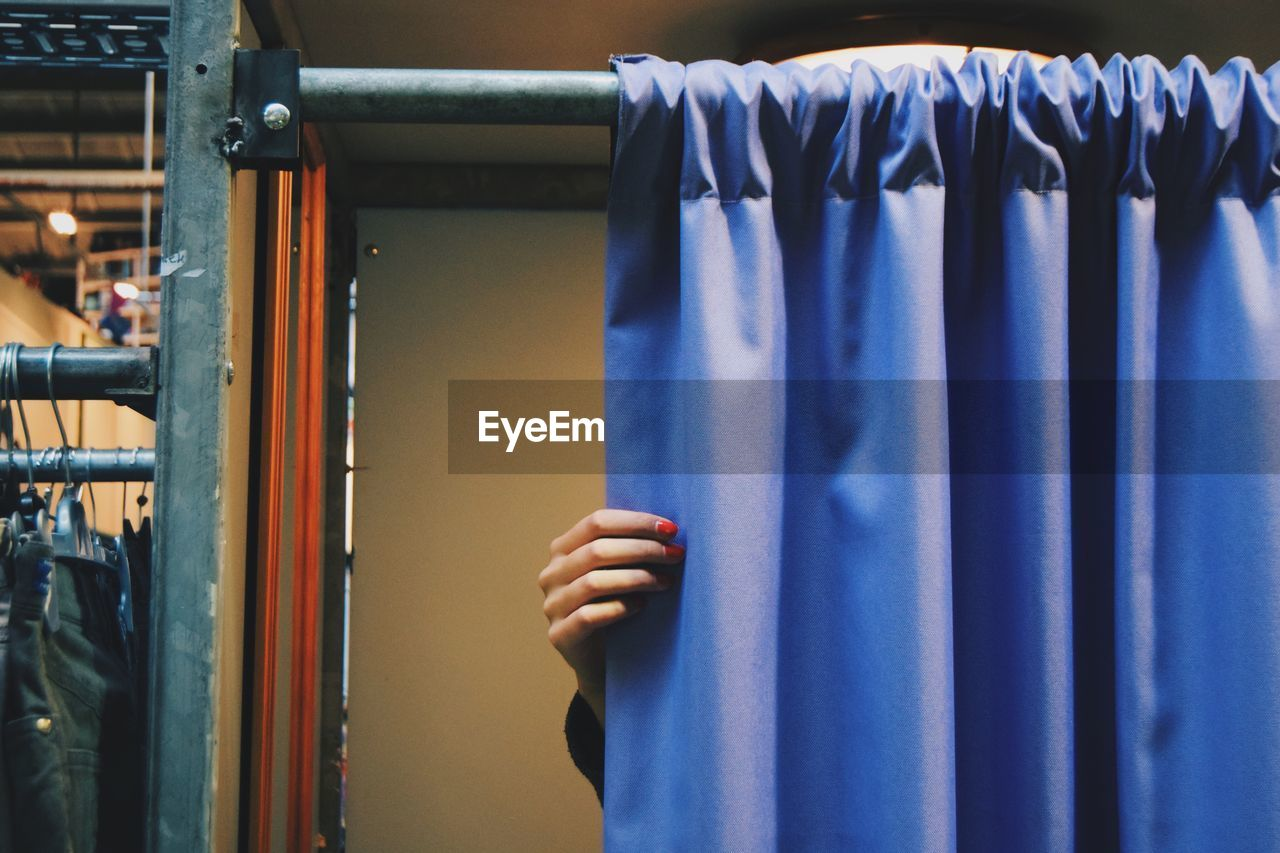 Cropped Hand Of Woman Closing Blue Curtain Of Changing Room