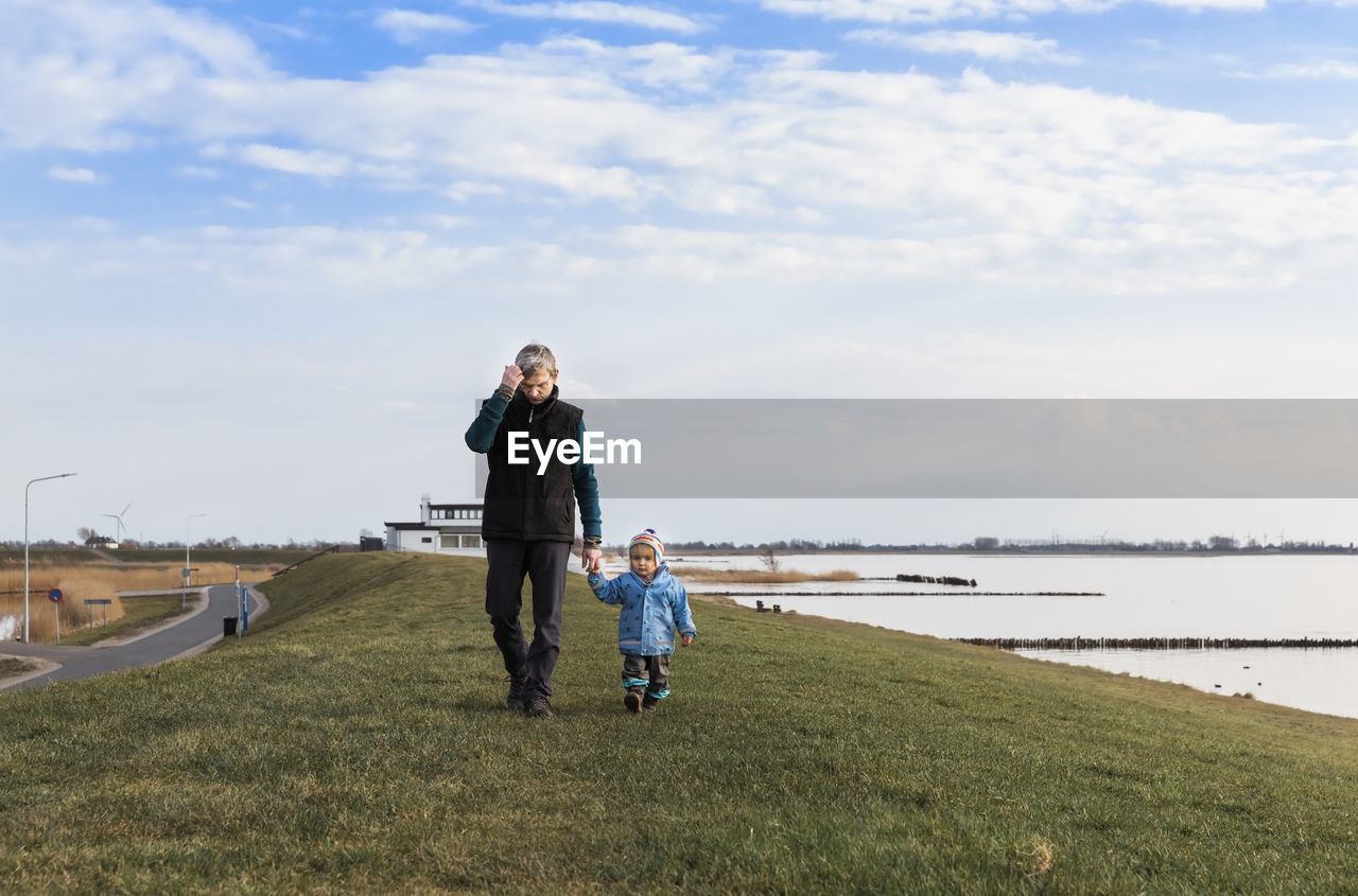 Grandfather And Granddaughter Walking At Lakeshore