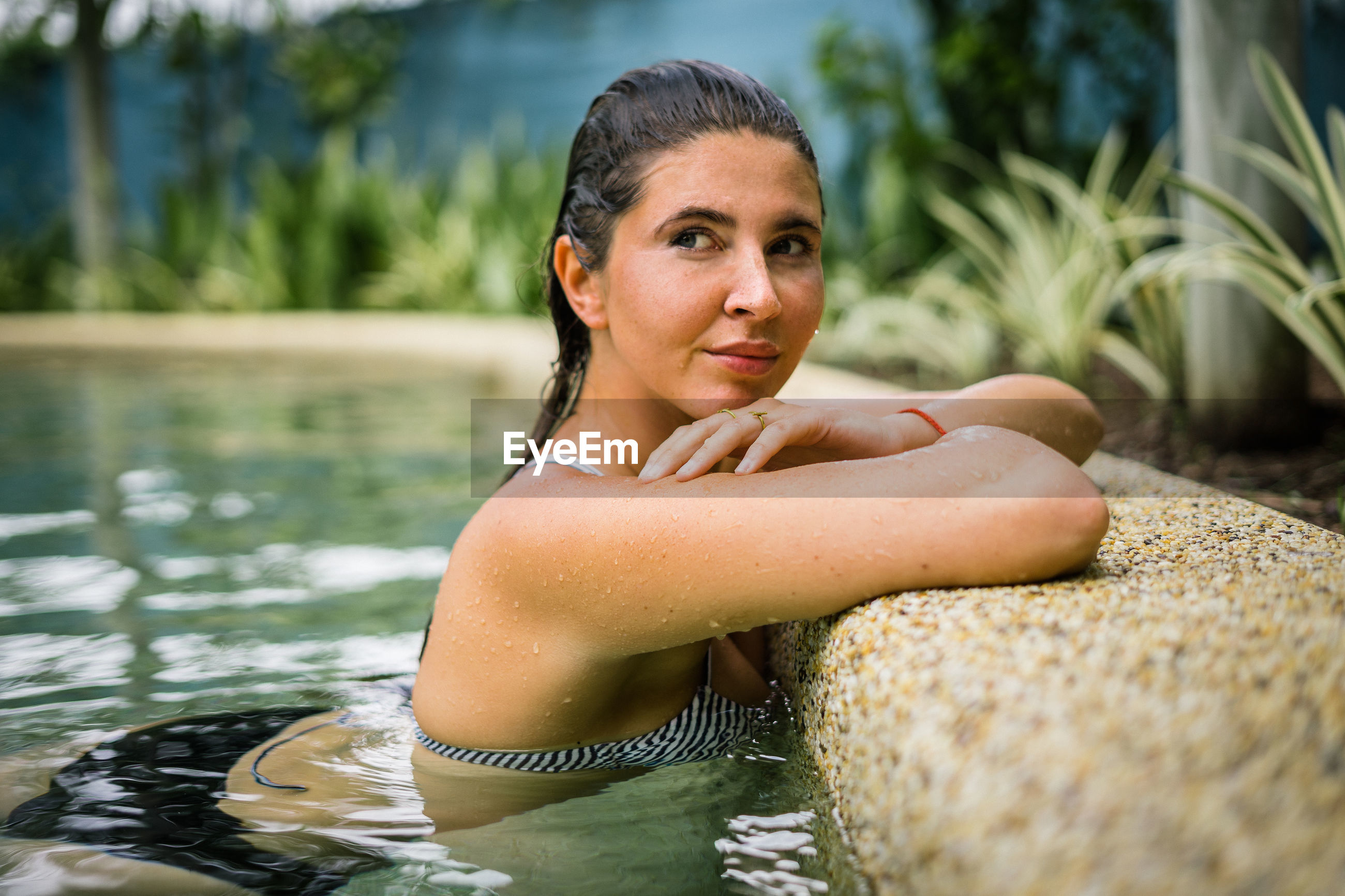 Smiling young woman looking away in swimming pool