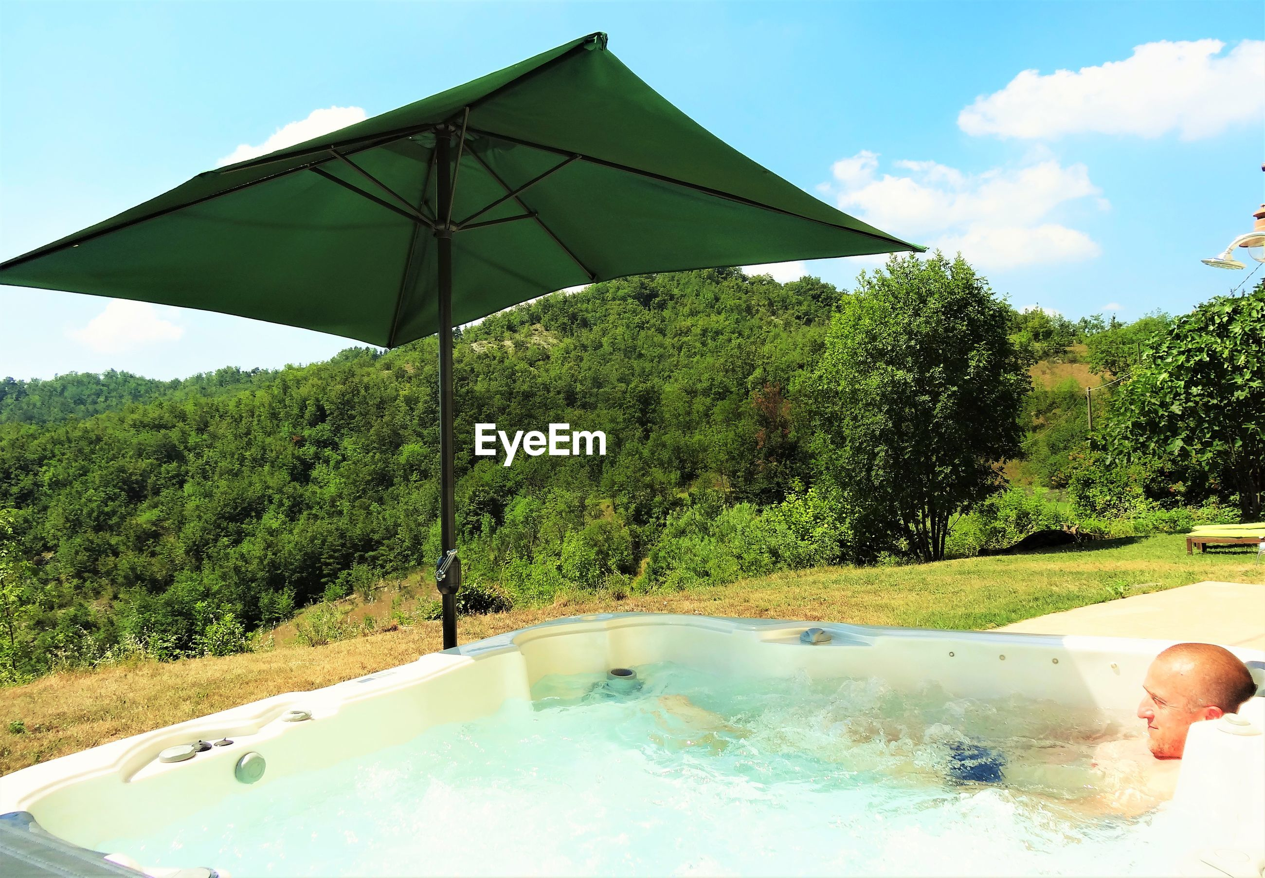 Man relaxing in hot tub on sunny day