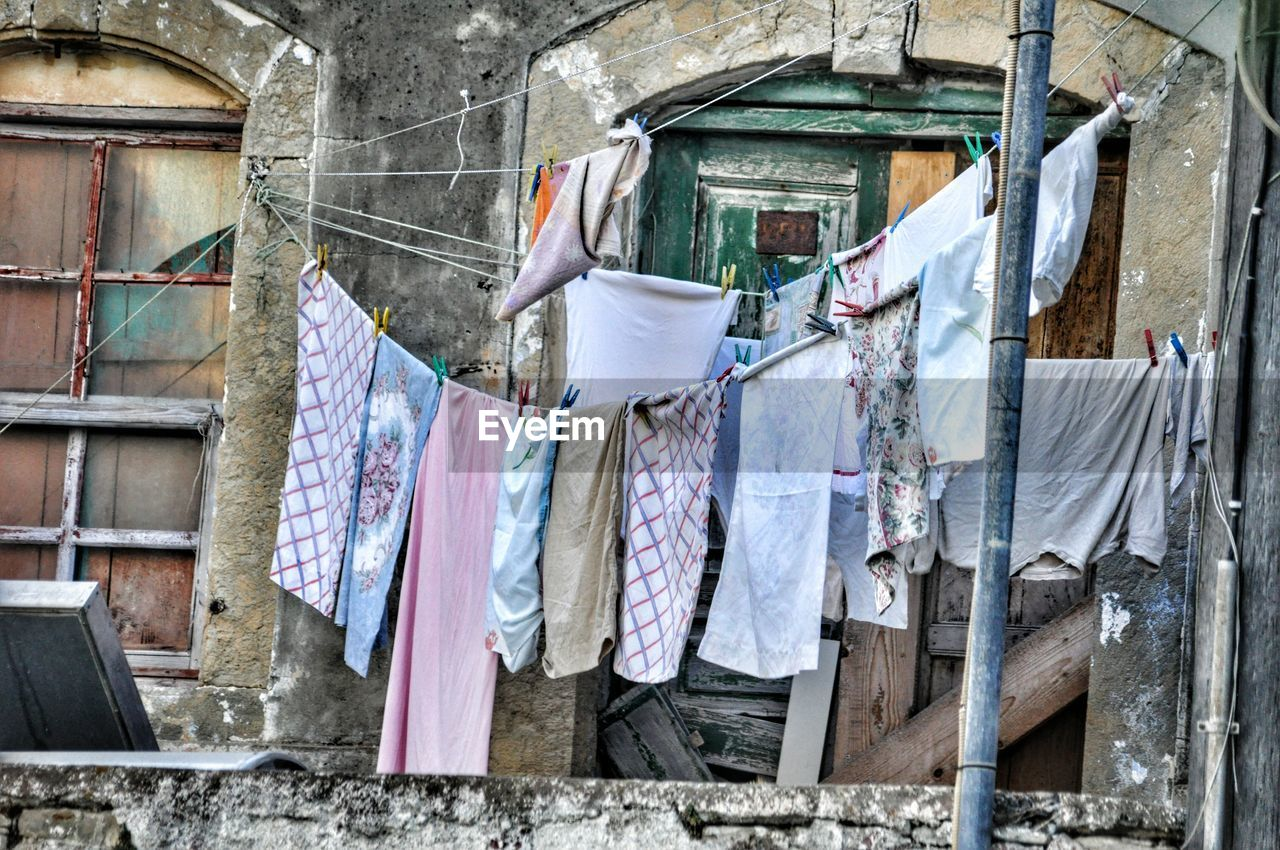 hanging, clothing, drying, laundry, clothesline, textile, built structure, architecture, building exterior, no people, day, building, washing, wall, cleaning, residential district, outdoors, city, house, clothespin, housework, clean