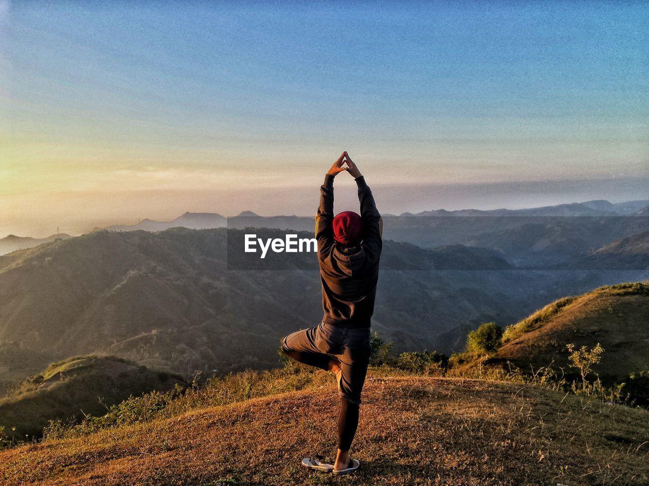 Rear View Of Man Doing Yoga Pose On Mountain