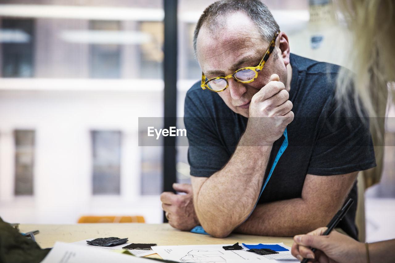 Designer listening during meeting at design studio