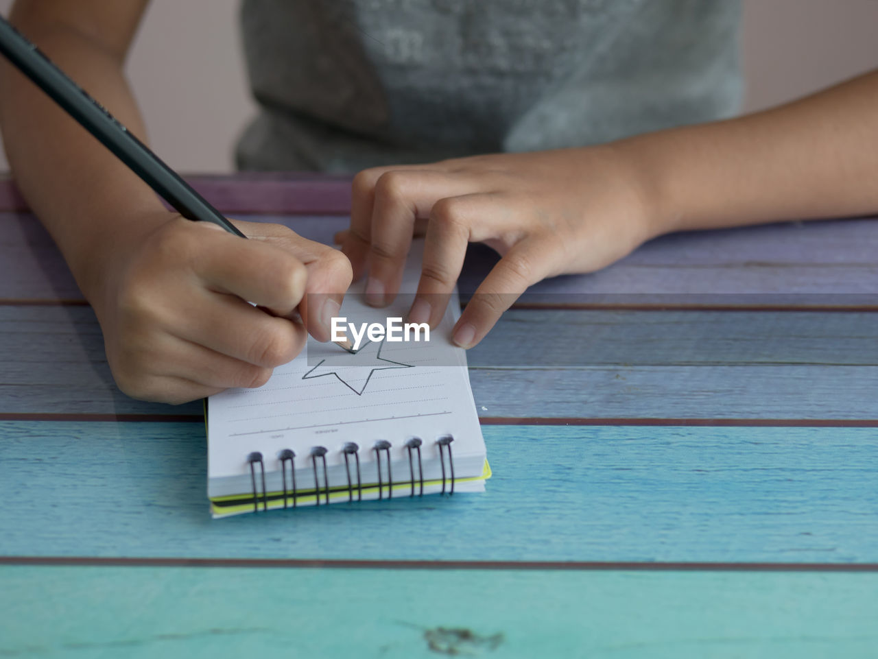 Cropped image of boy drawing in note pad on table