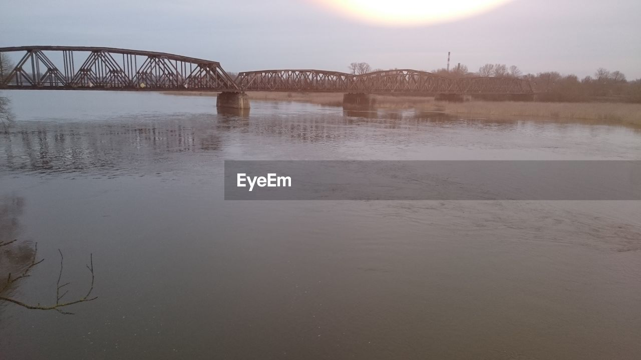 water, bridge - man made structure, river, connection, nature, built structure, outdoors, reflection, no people, sky, sunset, architecture, tranquility, beauty in nature, travel destinations, scenics, day, tree