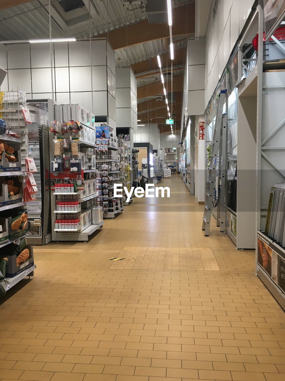 illuminated, flooring, indoors, the way forward, direction, absence, large group of objects, no people, architecture, empty, diminishing perspective, lighting equipment, ceiling, tiled floor, tile, store, choice, building, in a row, retail