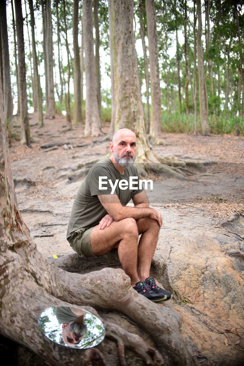 Full length portrait of man sitting by tree trunk in forest