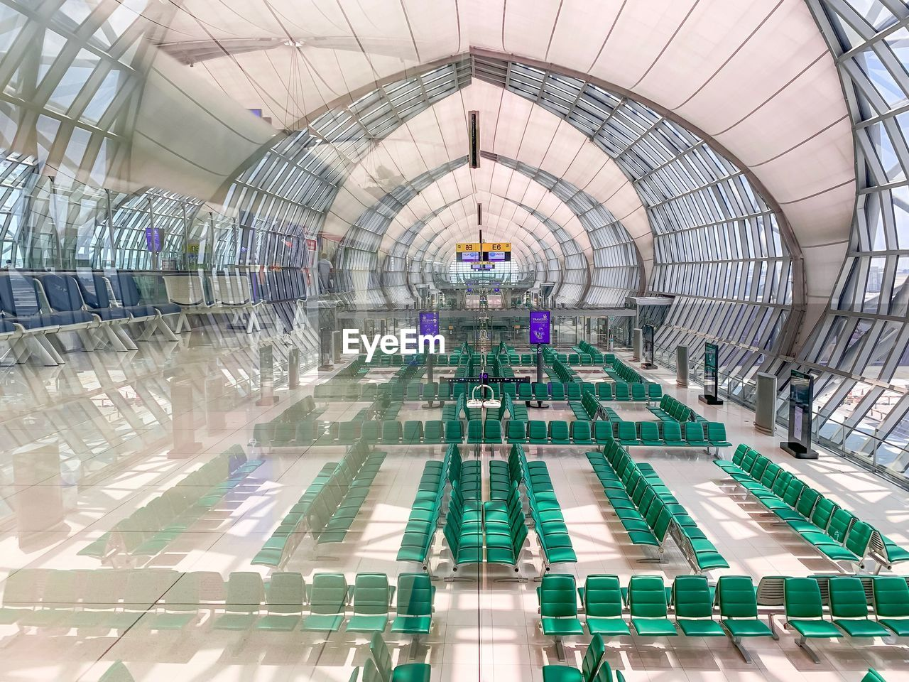 indoors, ceiling, architecture, glass - material, built structure, incidental people, real people, airport, transparent, flooring, illuminated, travel, high angle view, shopping mall, modern, day, group of people, large group of people, airport terminal