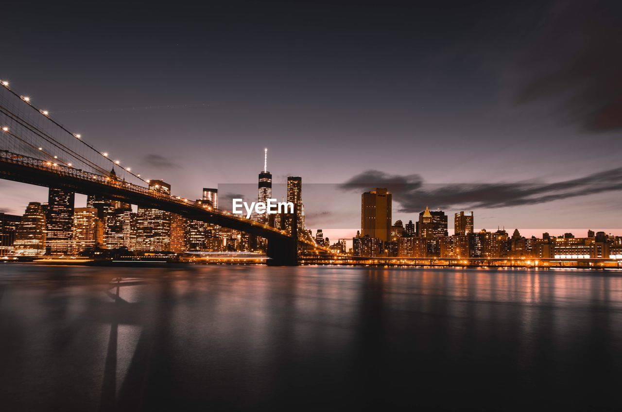 Illuminated Brooklyn Bridge Over East River In City Against Sky At Night