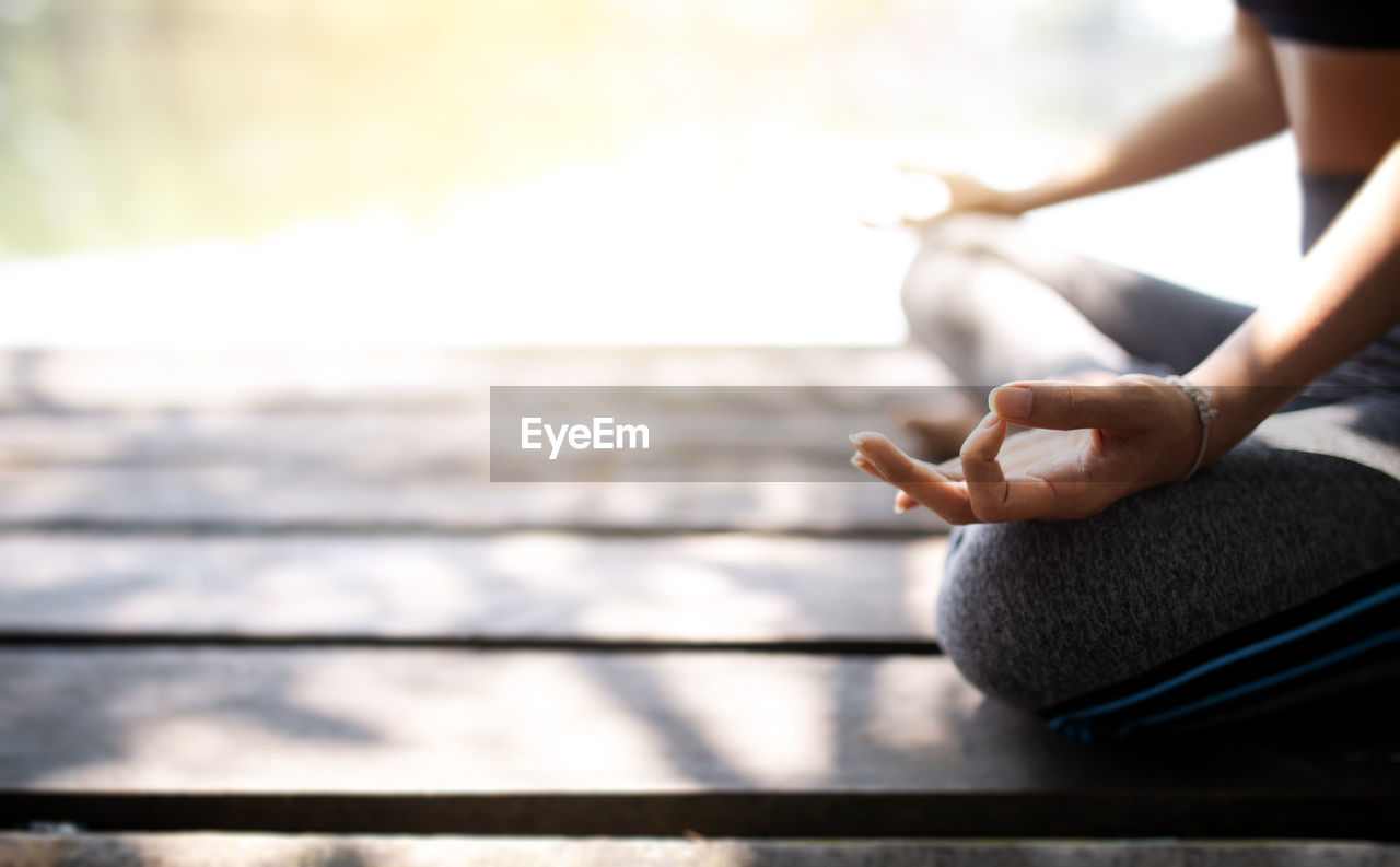 Midsection of woman doing yoga on pier during sunny day