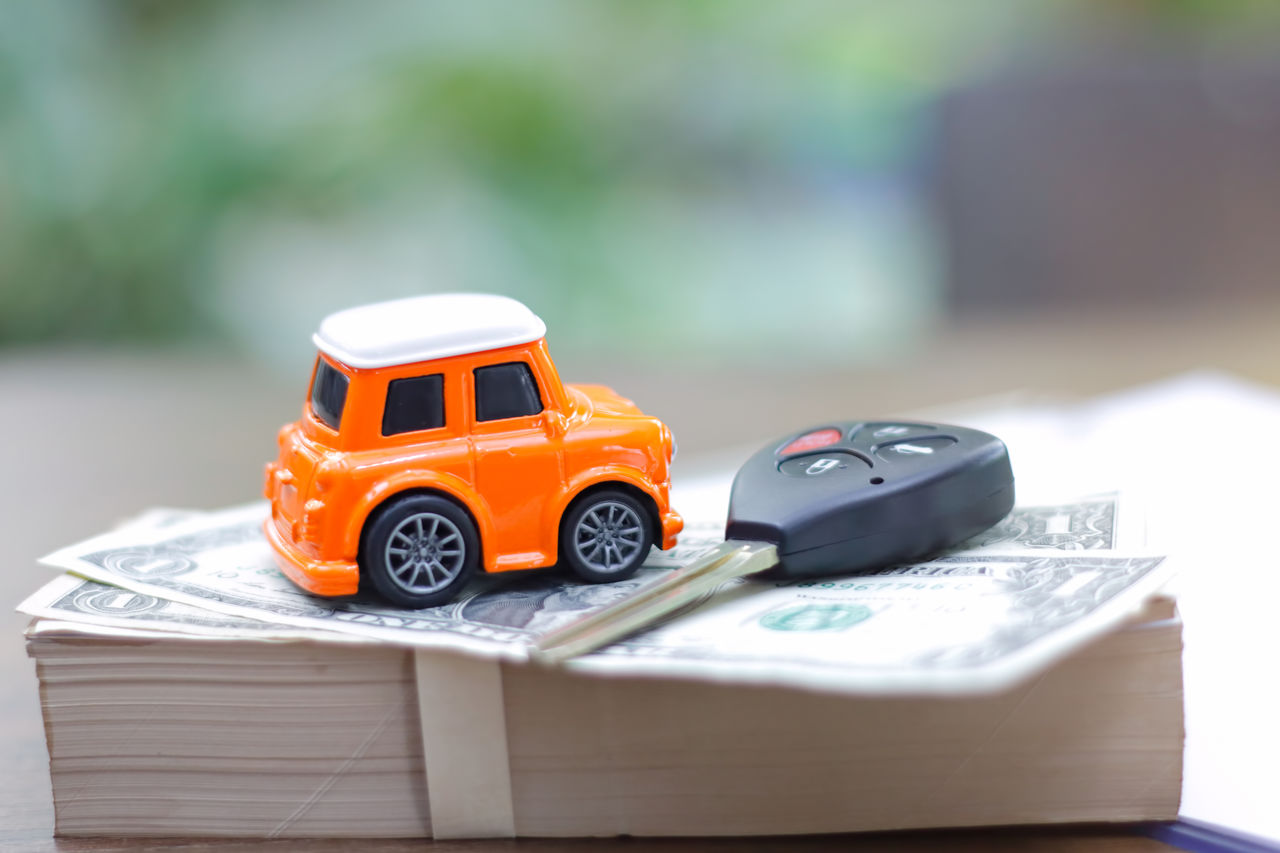 Close-up of toy car and key on currencies
