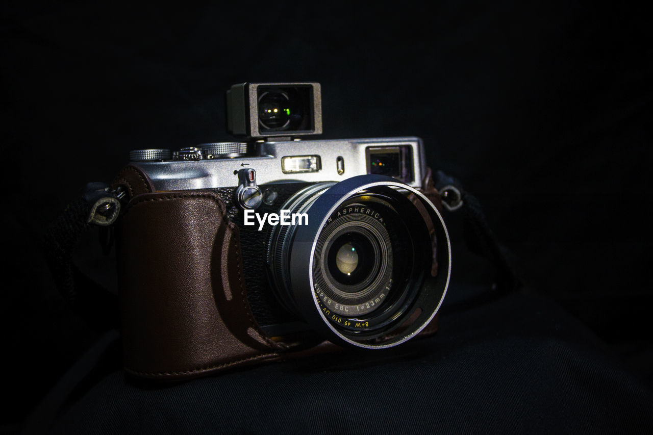 CLOSE-UP OF CAMERA ON BLACK BACKGROUND AGAINST GRAY