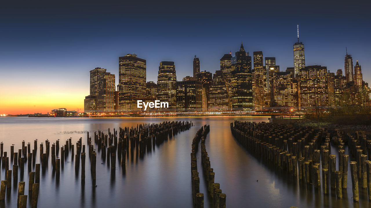 Wooden Posts In East River Against Manhattan Skyline During Sunset