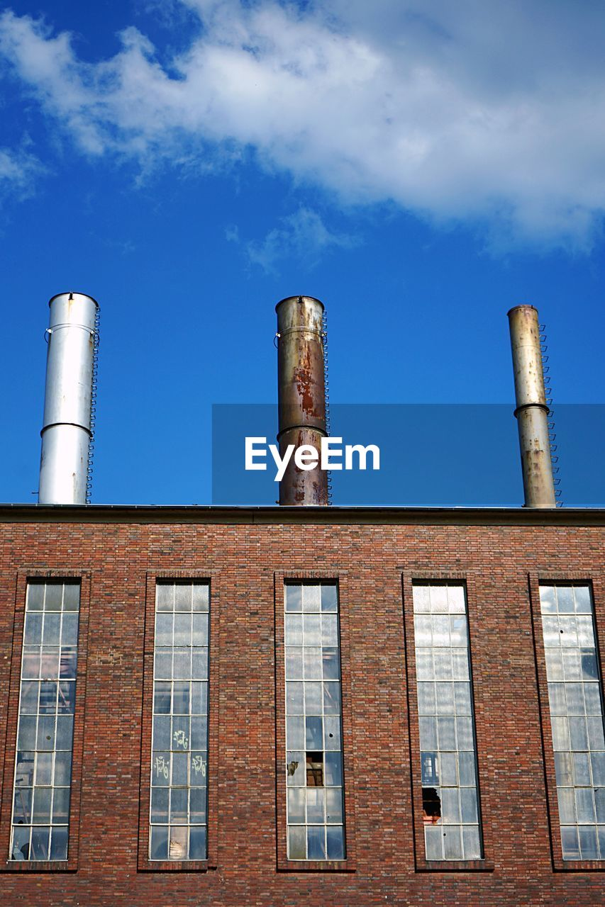 sky, building exterior, architecture, built structure, factory, smoke stack, industry, low angle view, cloud - sky, no people, blue, day, building, nature, outdoors, chimney, window, pollution, industrial building, tall - high