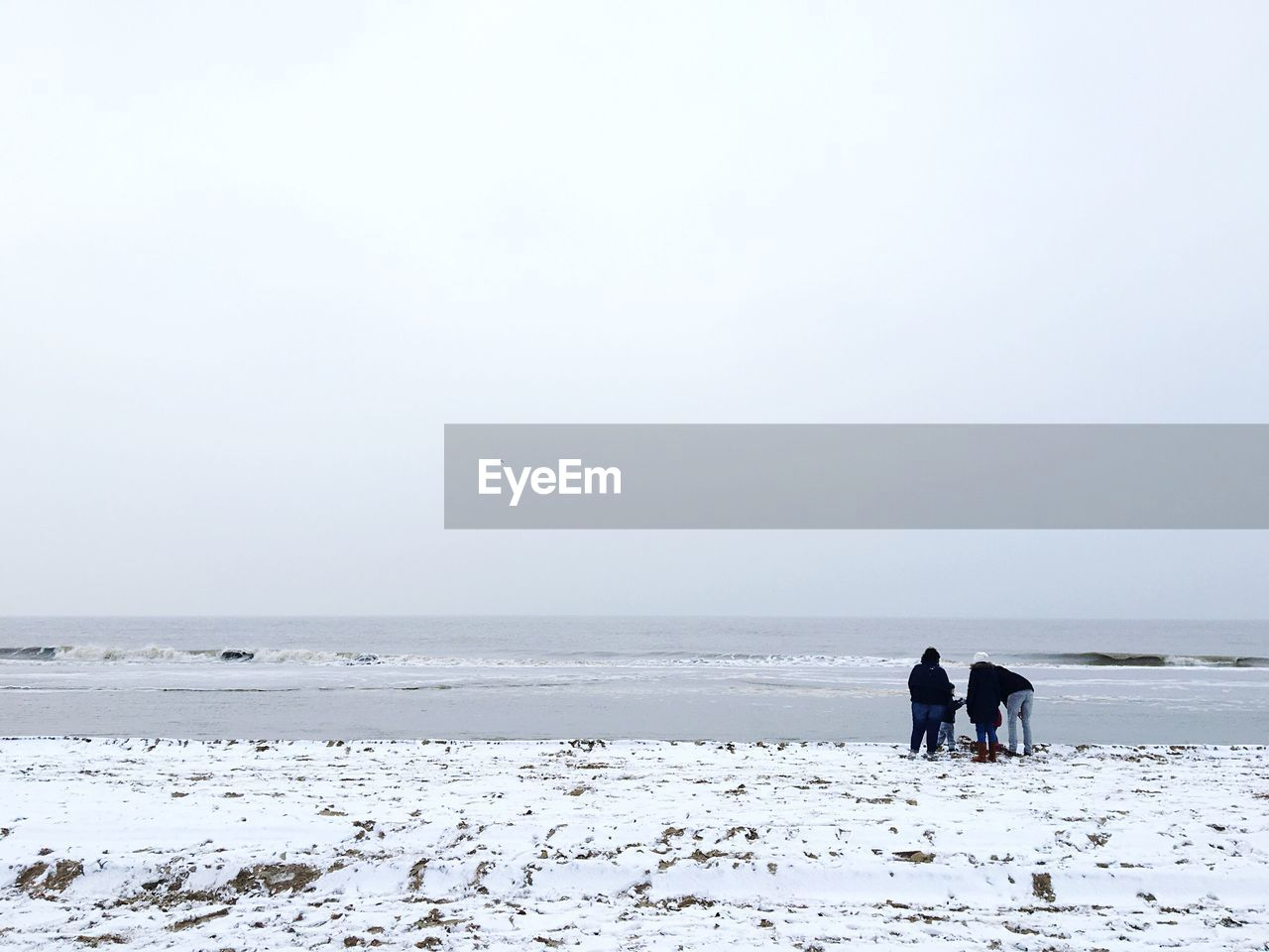 Family standing on shore at snow covered beach against sky during winter