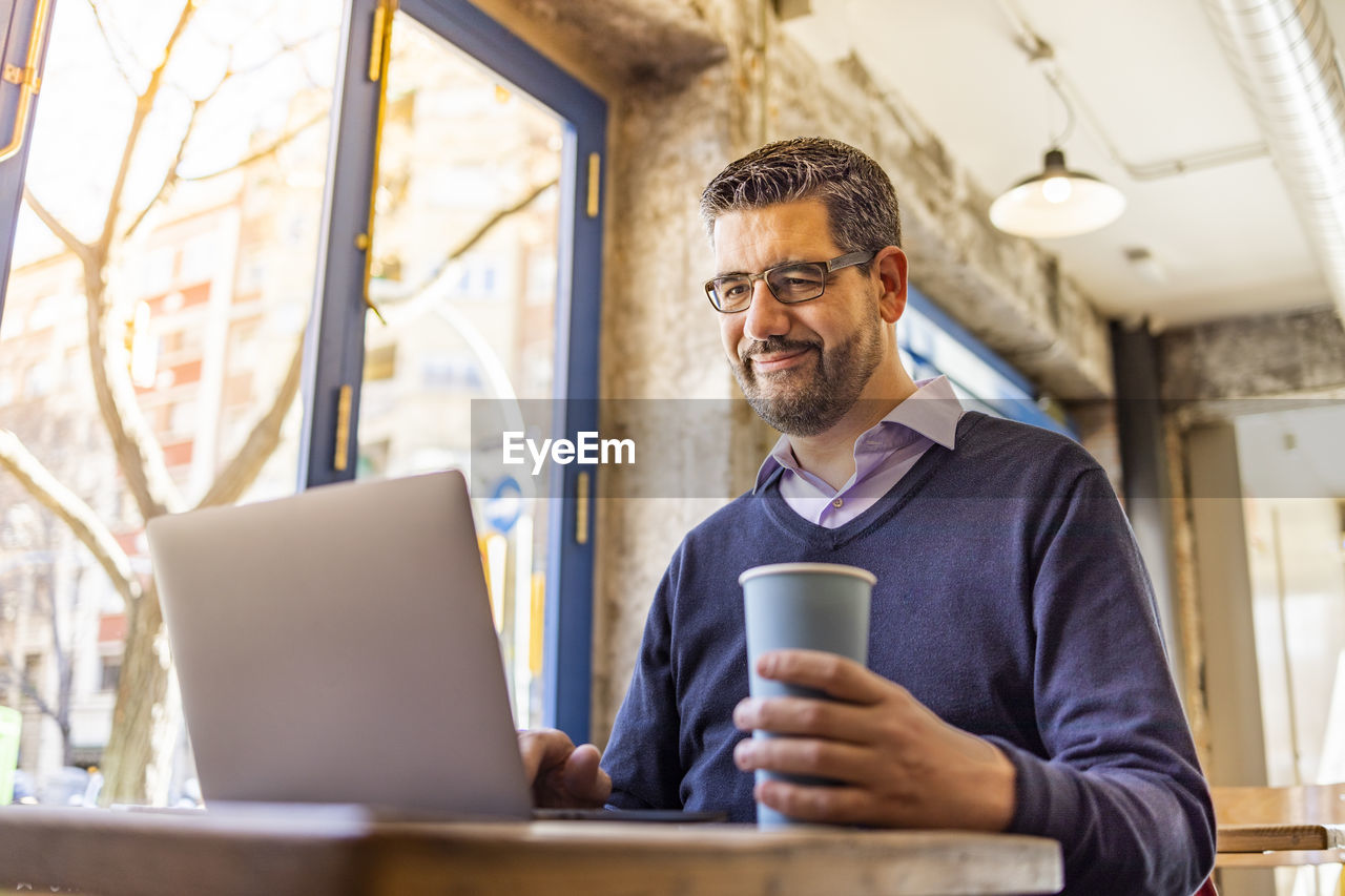 Businessman using laptop at table in cafe