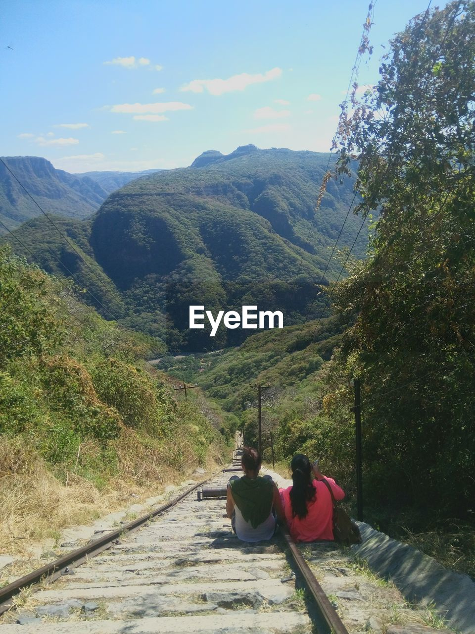 Rear View Of Friends Sitting On Railroad Track Against Mountain