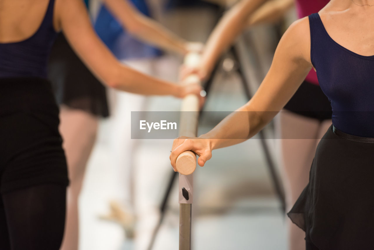 Midsection Of Ballerinas Practicing In Studio
