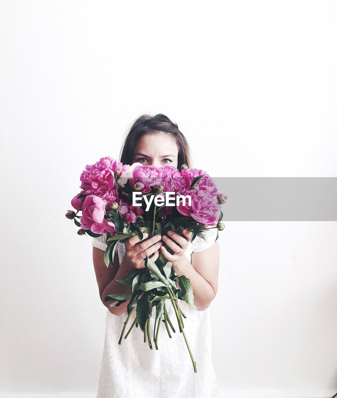 flowering plant, flower, plant, one person, white background, indoors, front view, vulnerability, beauty in nature, freshness, fragility, flower arrangement, studio shot, portrait, copy space, looking at camera, holding, nature, bouquet, flower head, hairstyle, bunch of flowers