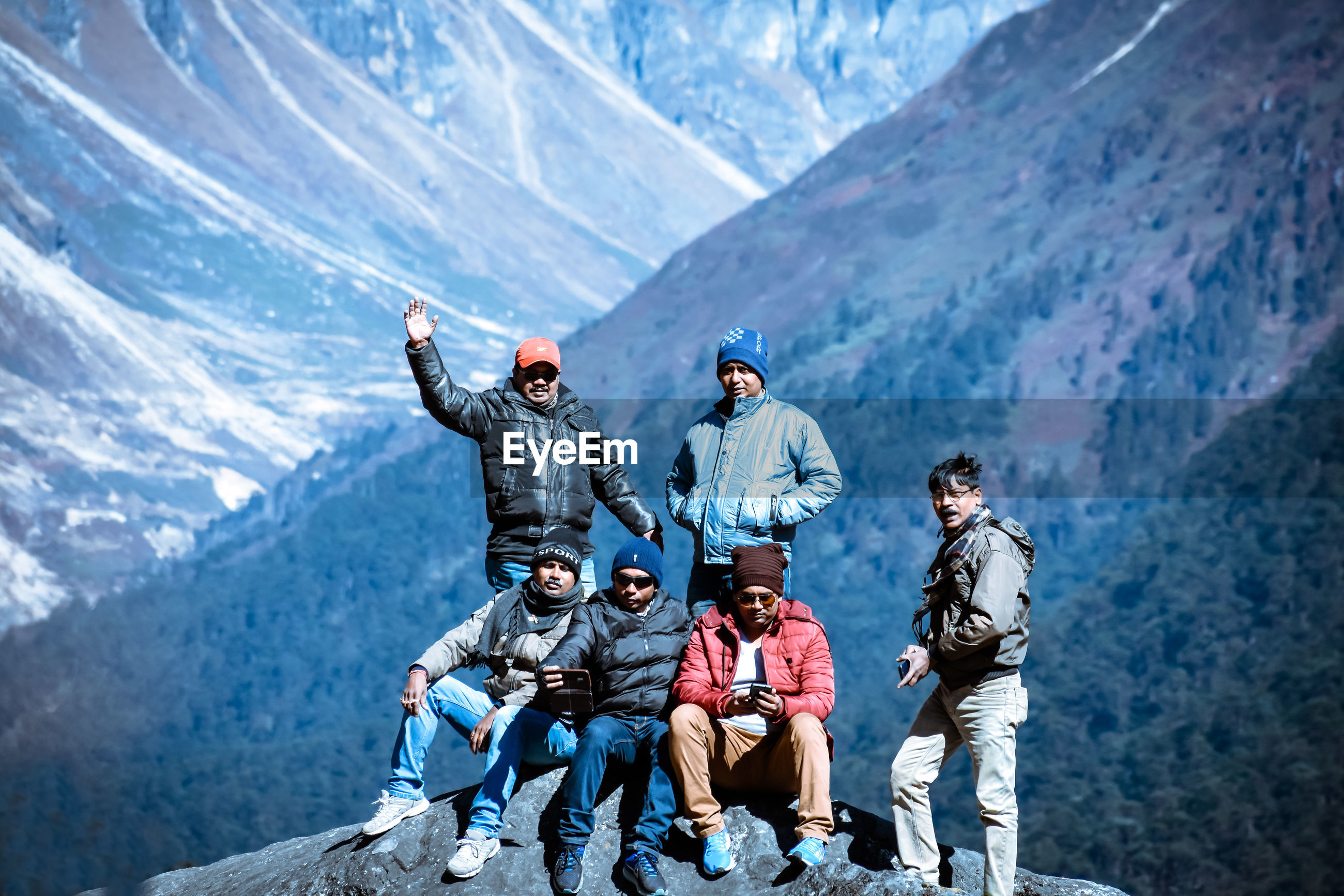 PEOPLE ON SNOW COVERED MOUNTAINS AGAINST MOUNTAIN