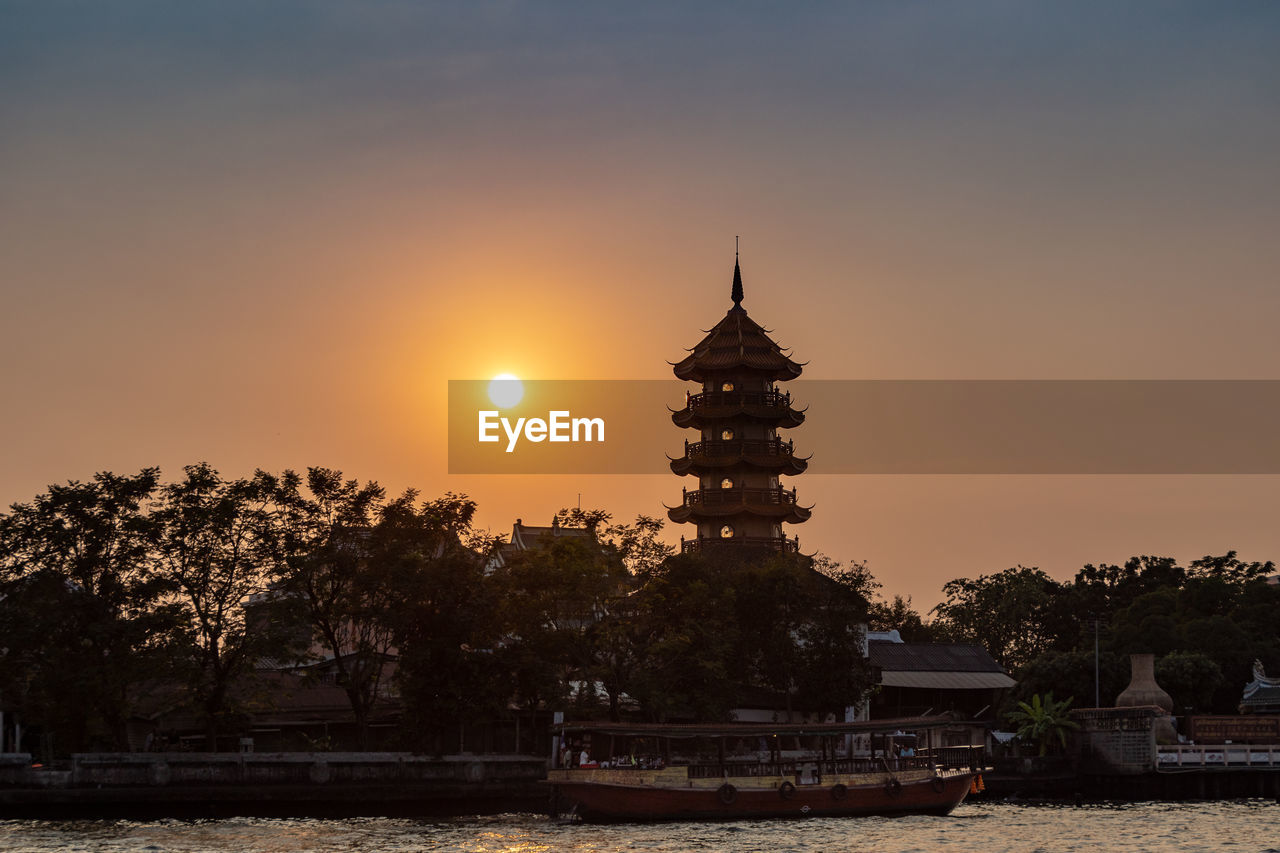 sky, sunset, tree, architecture, built structure, religion, belief, place of worship, plant, water, building exterior, nature, orange color, sun, spirituality, building, no people, waterfront, outdoors