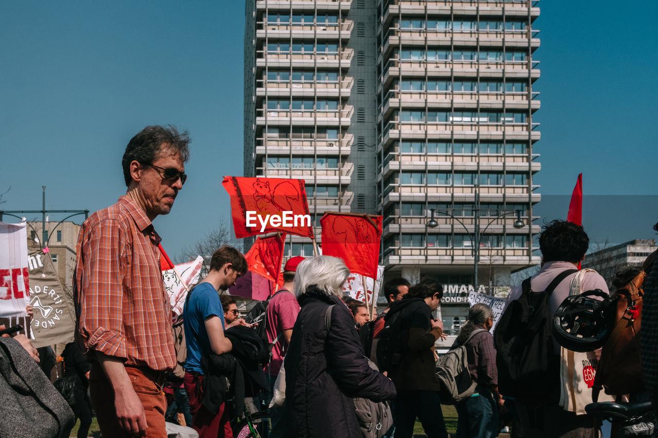 PEOPLE STANDING AGAINST BUILDINGS