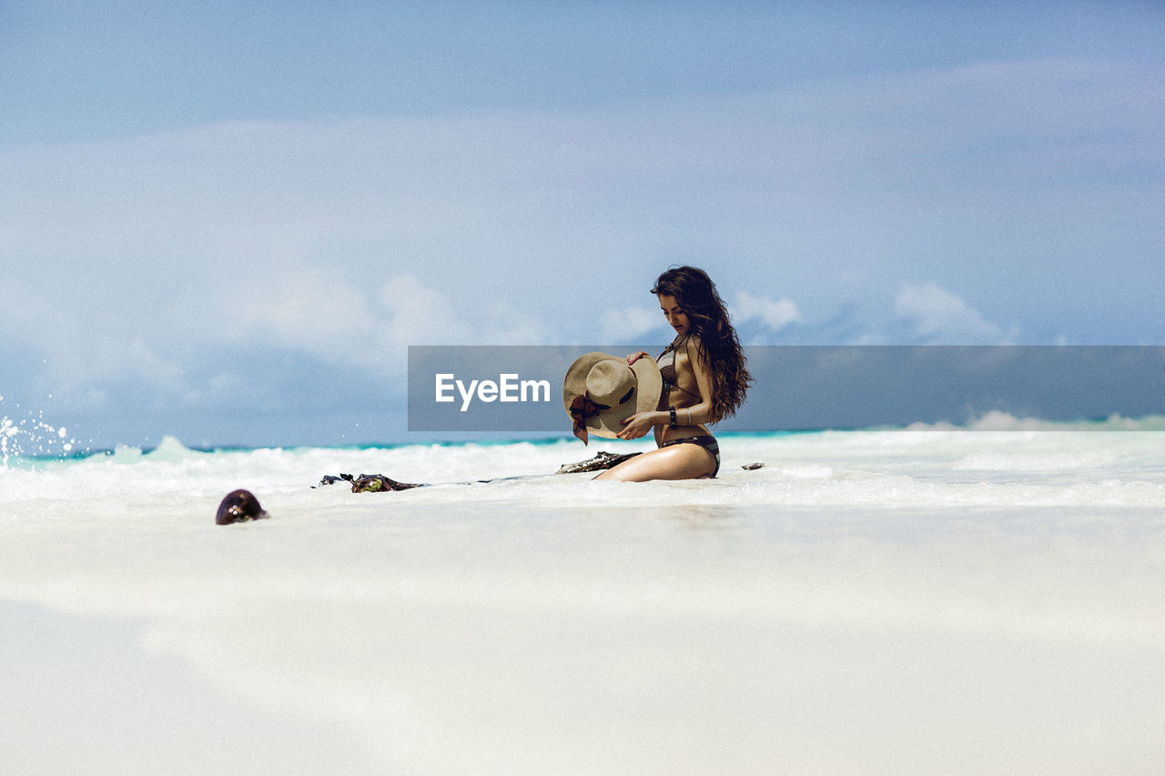 Surface Level Of Young Woman In Bikini Sitting On Shore At Beach Against Sky