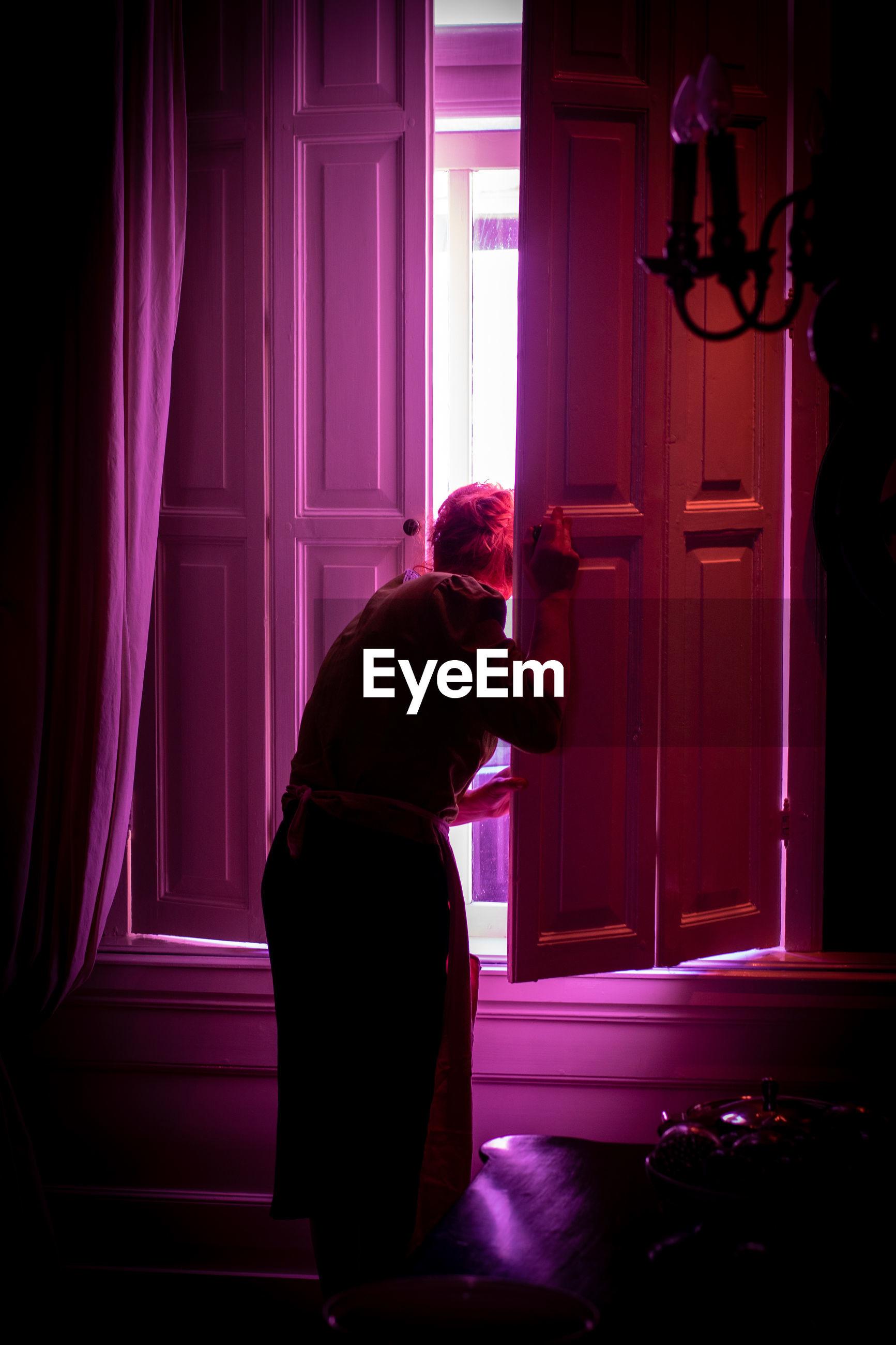 SIDE VIEW OF WOMAN STANDING AGAINST WINDOW IN DARK ROOM