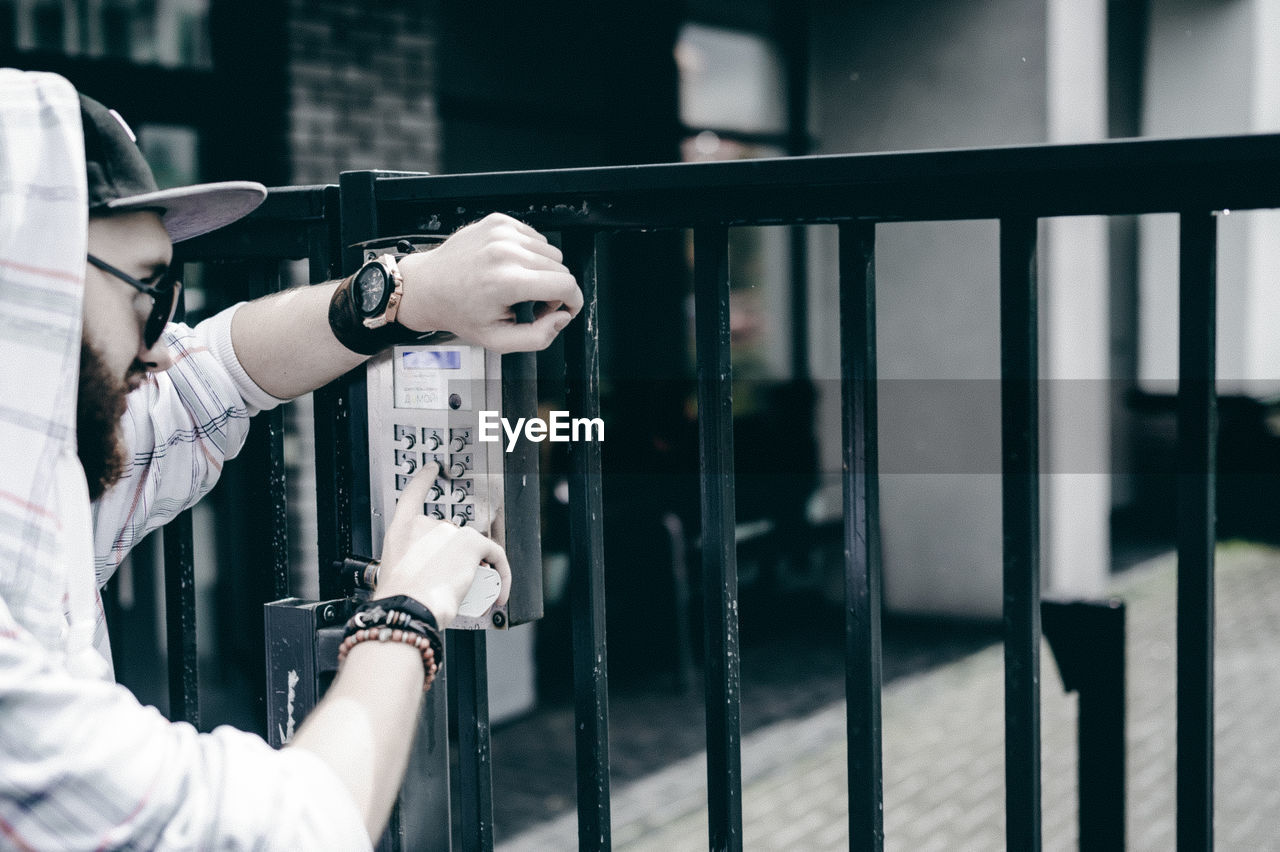 Young Man Entering Password In Security System On Gate