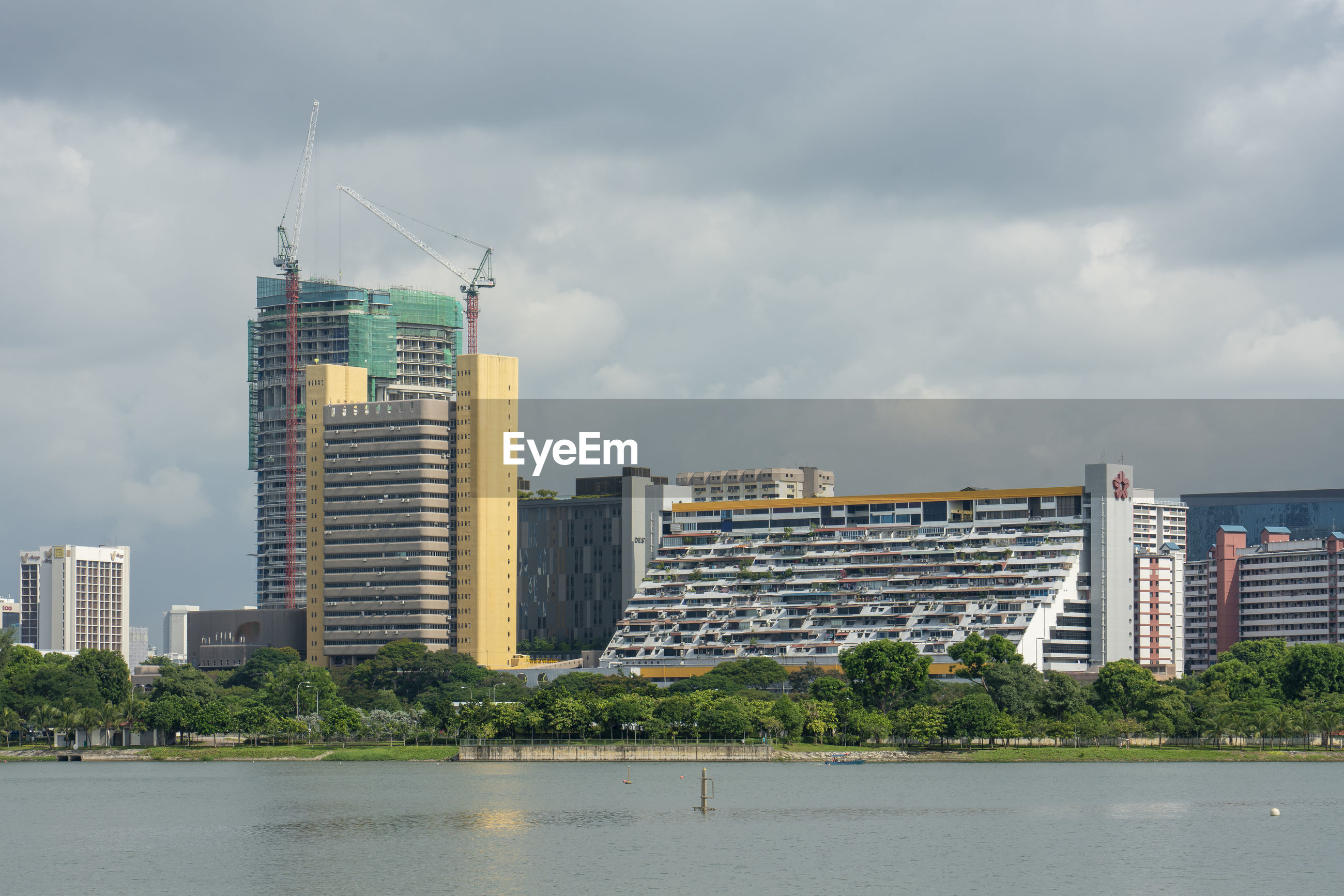 Buildings at waterfront in city against sky