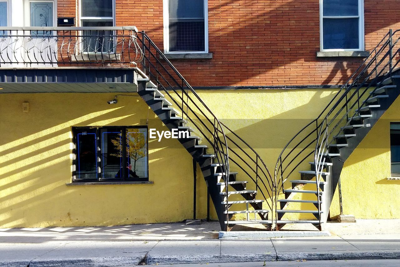 architecture, built structure, building exterior, building, staircase, sunlight, day, shadow, yellow, railing, no people, window, outdoors, steps and staircases, city, residential district, nature, wall, entrance, sunny