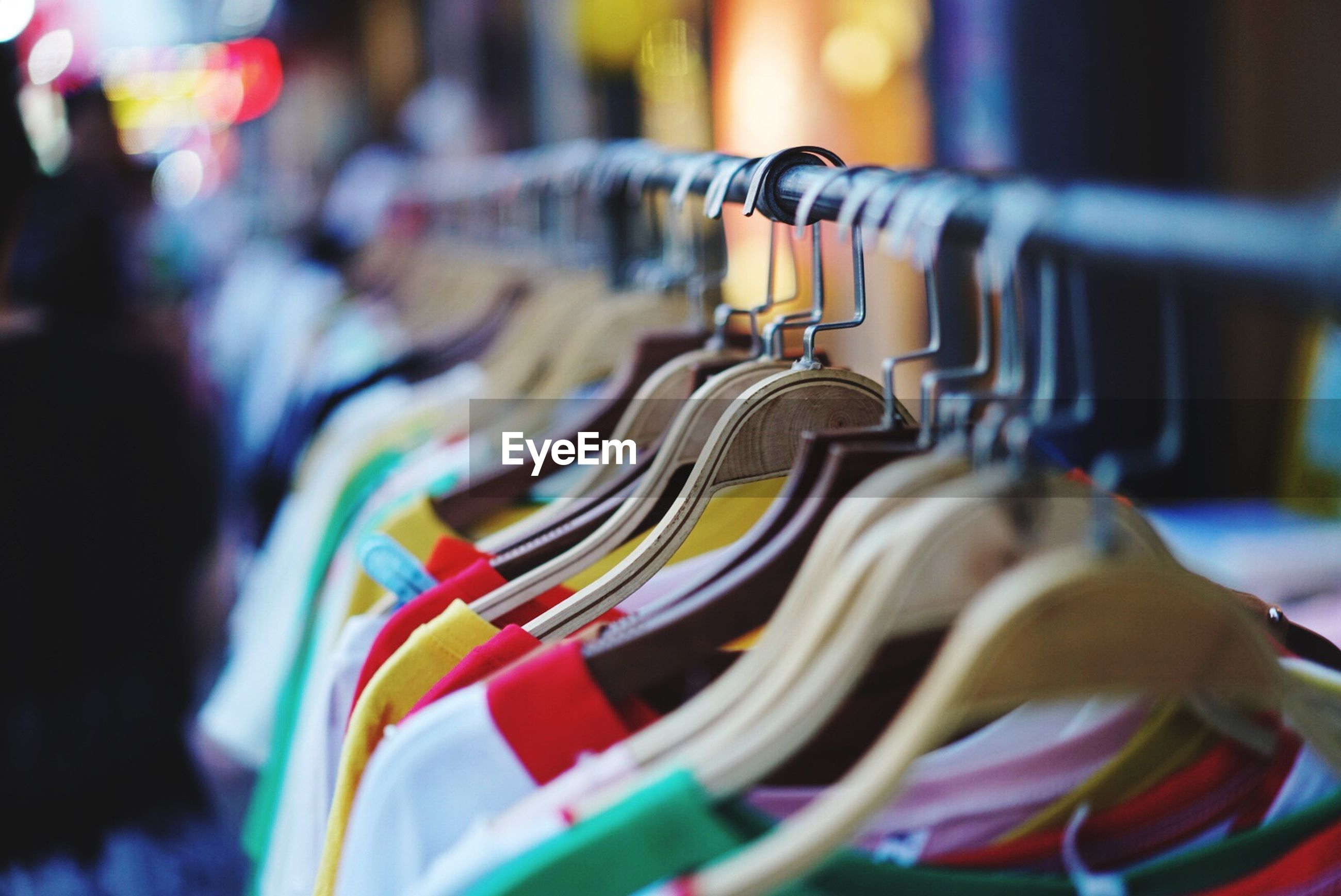 in a row, variation, choice, retail, hanging, multi colored, large group of objects, store, clothing, coathanger, selective focus, for sale, no people, indoors, close-up, consumerism, day