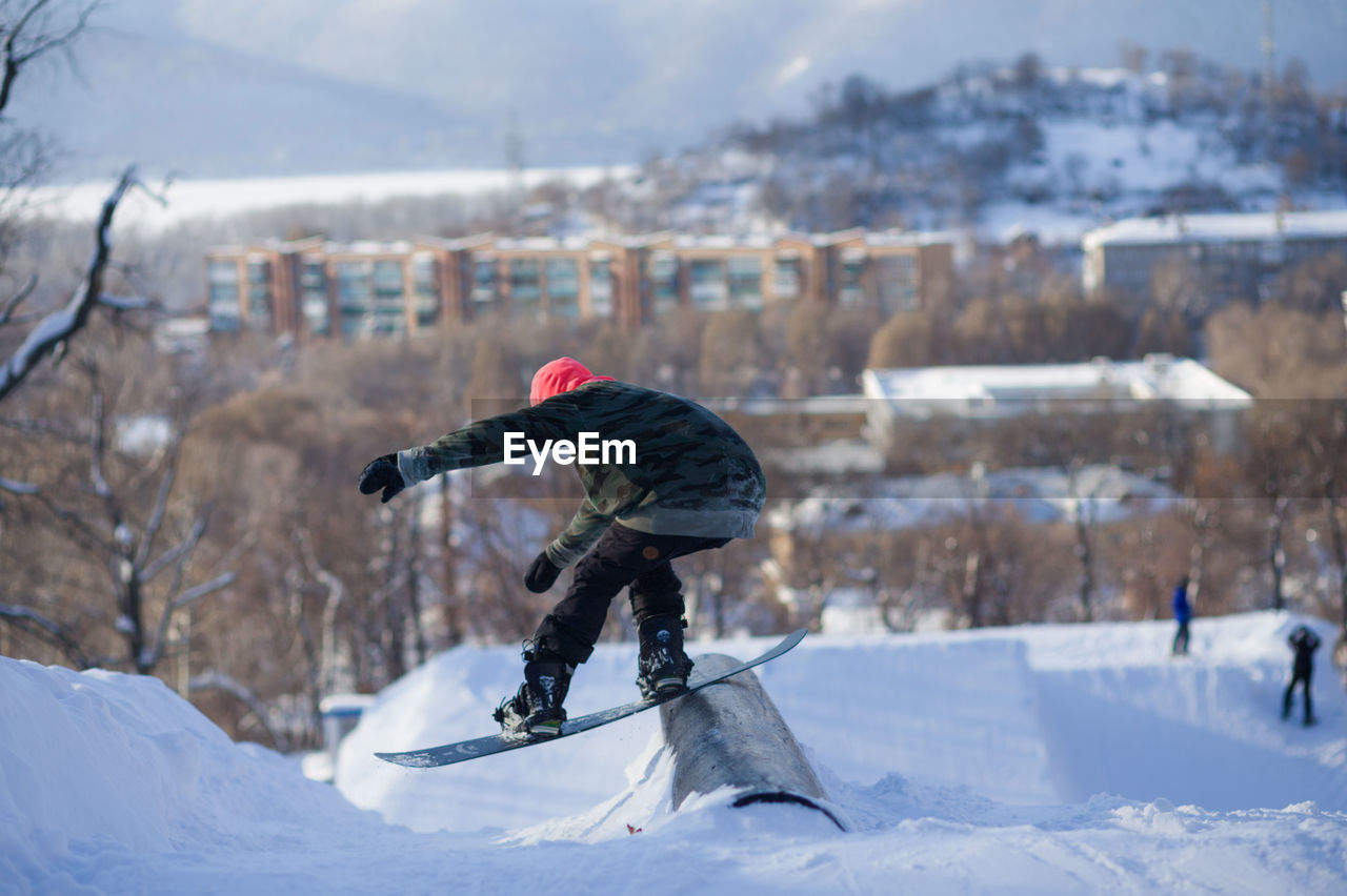 snow, cold temperature, winter, sport, mountain, day, nature, leisure activity, real people, focus on foreground, one person, extreme sports, winter sport, building exterior, full length, skill, sports equipment, outdoors, warm clothing