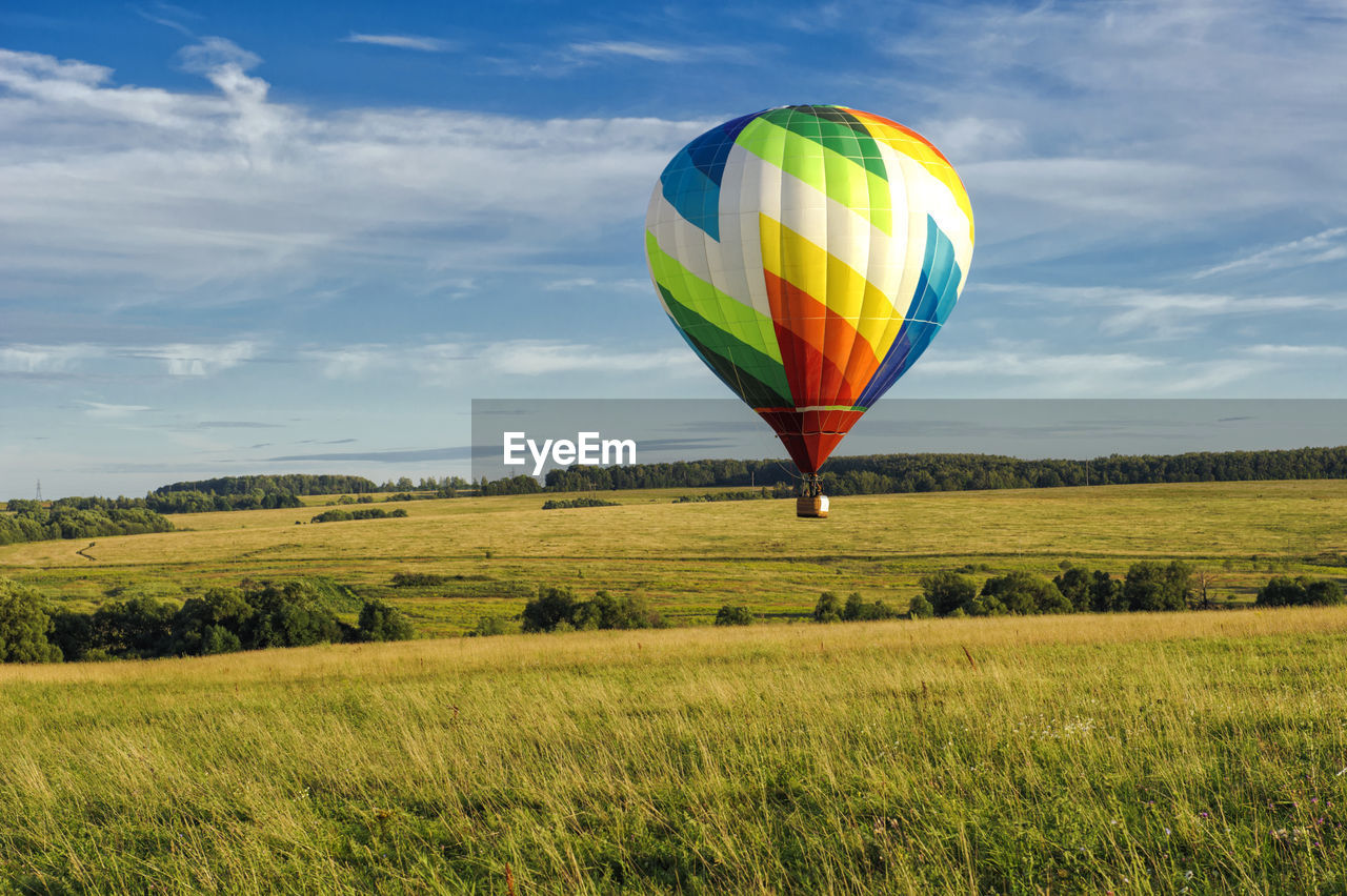 hot air balloon, balloon, land, field, air vehicle, flying, sky, landscape, plant, environment, cloud - sky, nature, multi colored, adventure, scenics - nature, grass, mid-air, green color, day, transportation, freedom, outdoors, ballooning festival